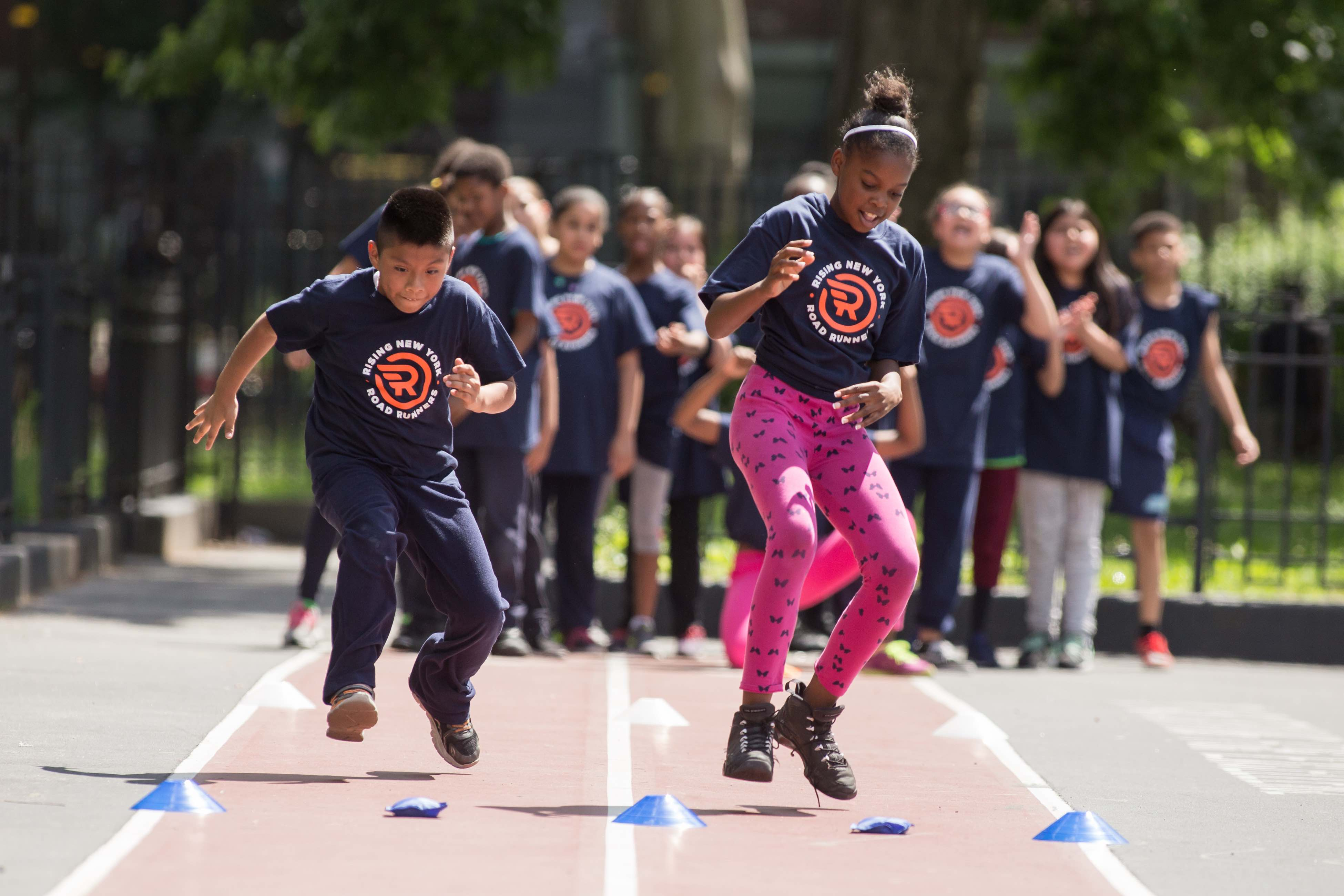 Two Rising New York Road Runners students taking part in fitness activities on a playground track