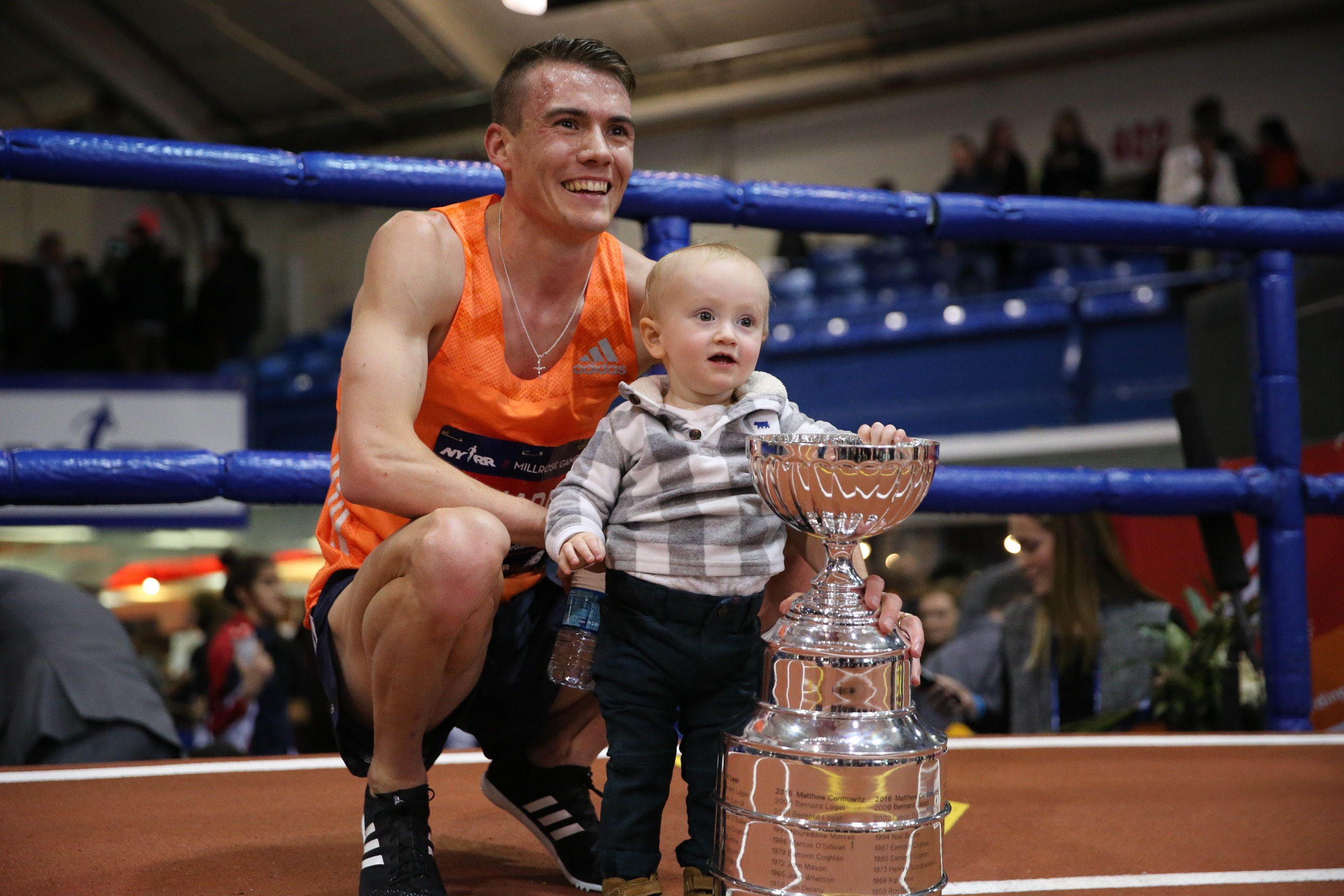 Chris O'Hare with his son and the NYRR Wanamaker Mile trophy at the NYRR Millrose Games