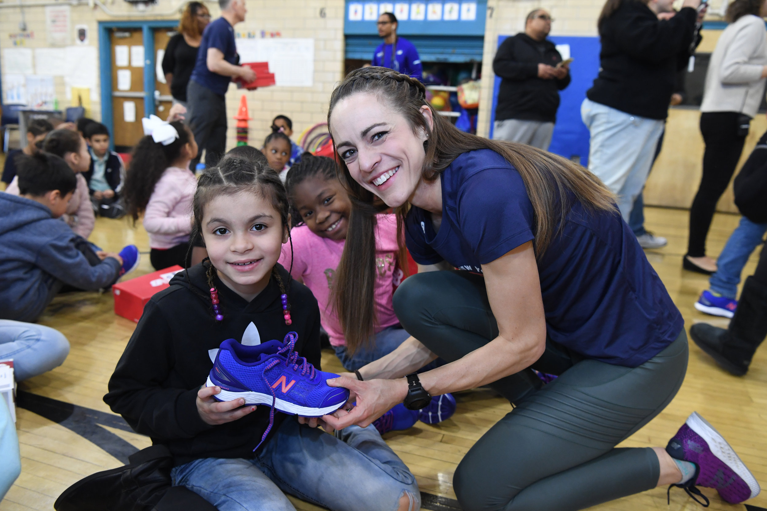 Jenny Simpson giving a pair of New Balance shoes to a Rising New York Road Runners participant at the 1 for You 1 for Youth shoe distribution in Red Hook.