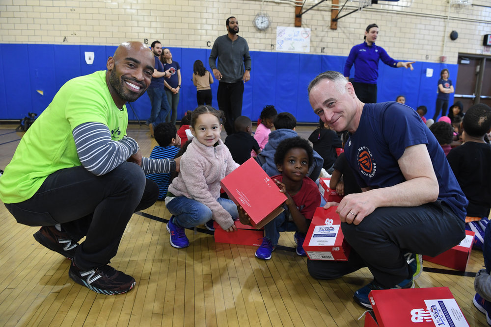 Tiki Barber and Michael Capiraso distribute free New Balance sneakers to students of PS 676K in Red Hook, Brooklyn.
