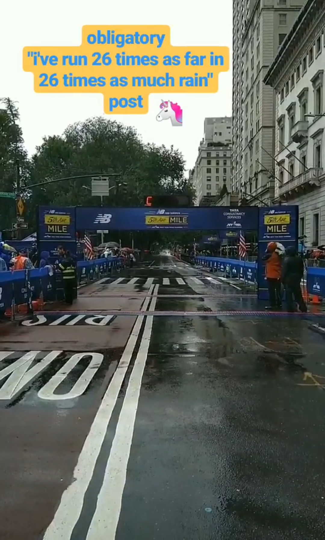 """An image of the 2018 New Balance 5th Avenue Mile finish line with text overlaid: """"obligatory 'i've run 26 times as far in 26 times as much rain' post"""""""