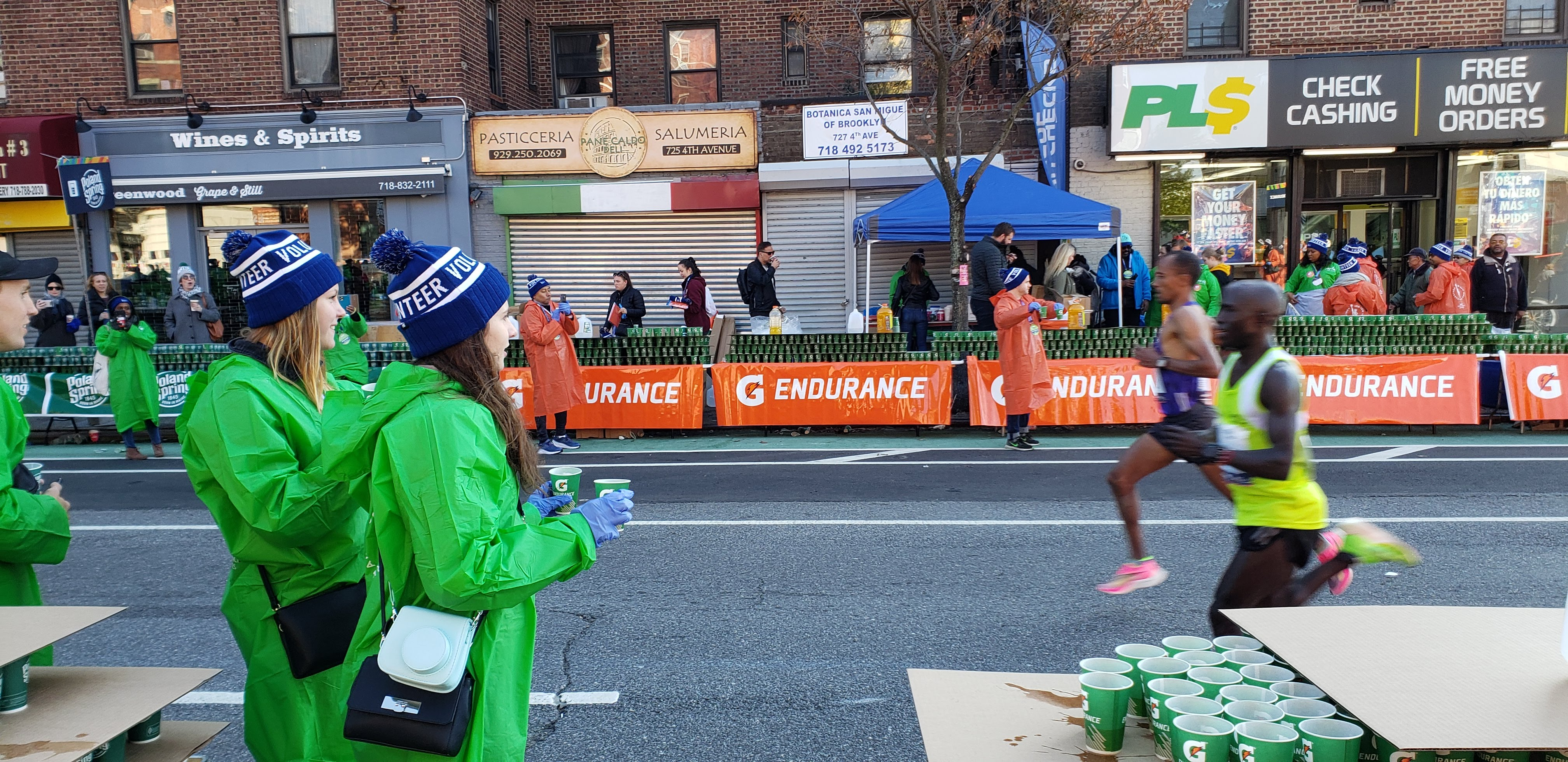 Volunteers with the Exchange Visitor Program hand out water to runners in the TCS NYC Marathon.