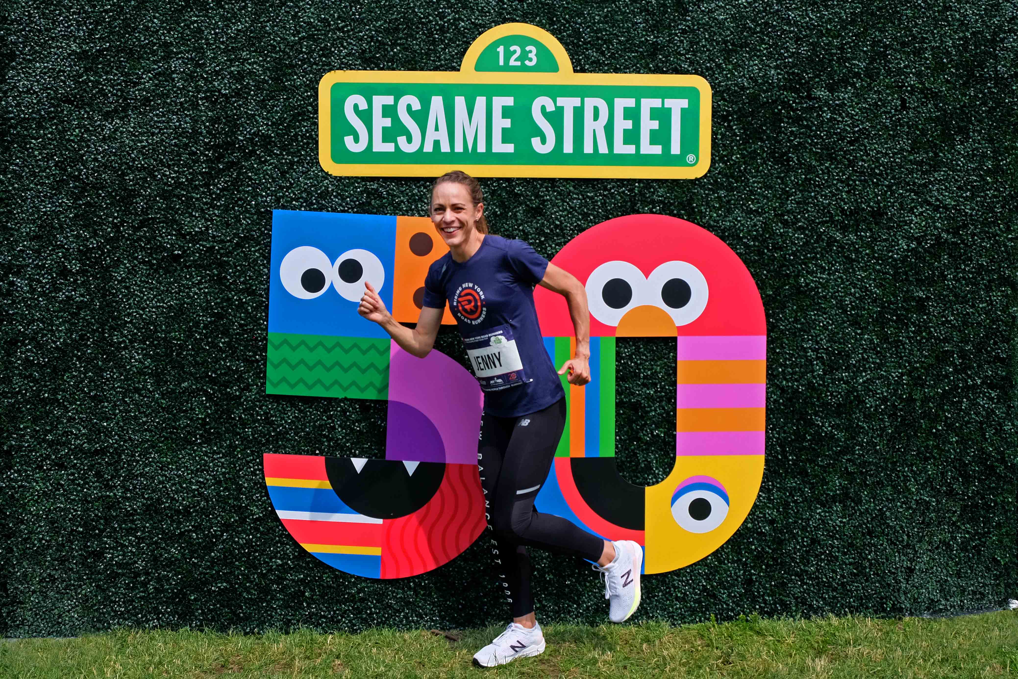 Jenny Simpson in front of the Sesame Street 50th Anniversary logo