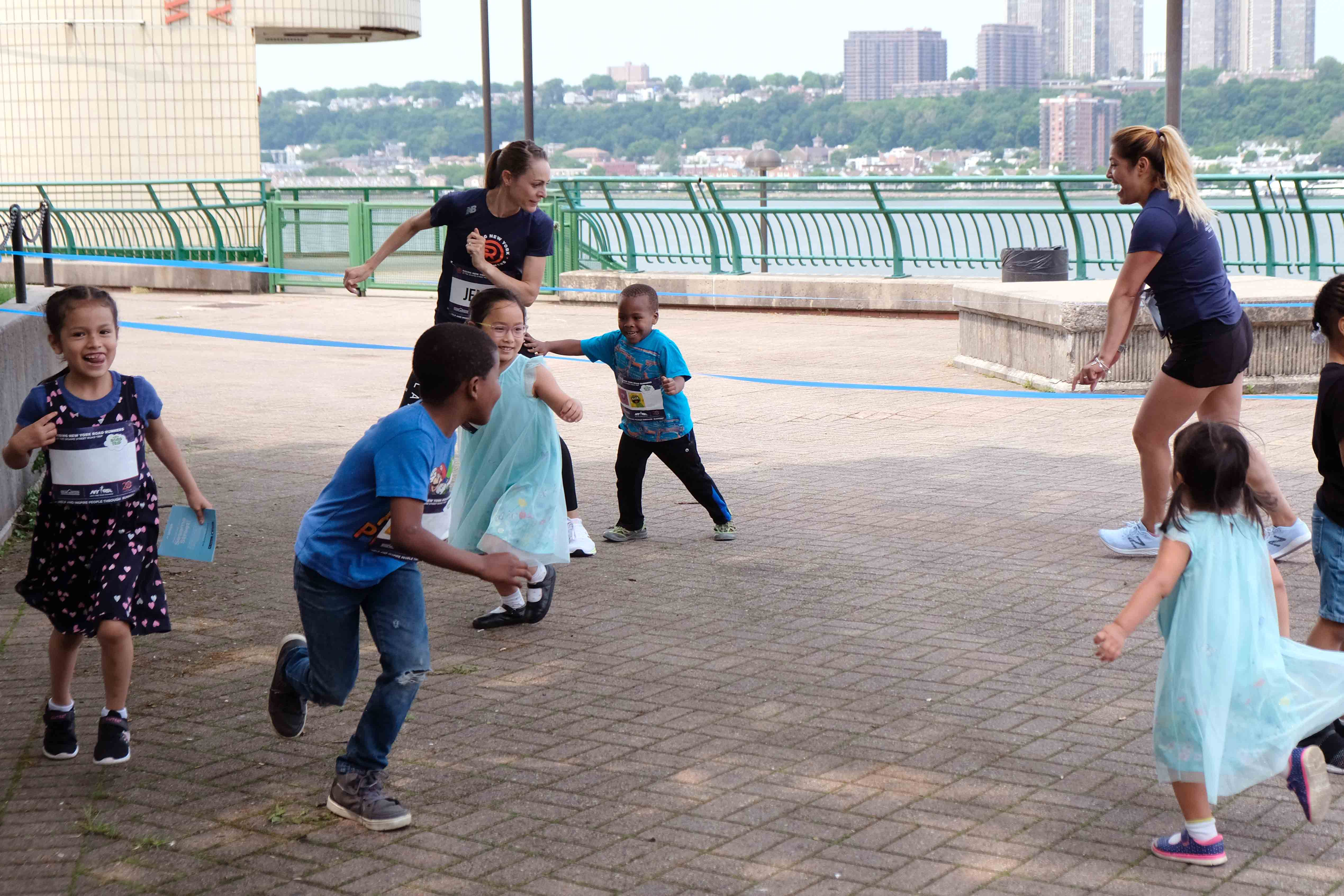 Rising New York Road Runners students playing a game of tag with Jenny Simpson and NYRR staff
