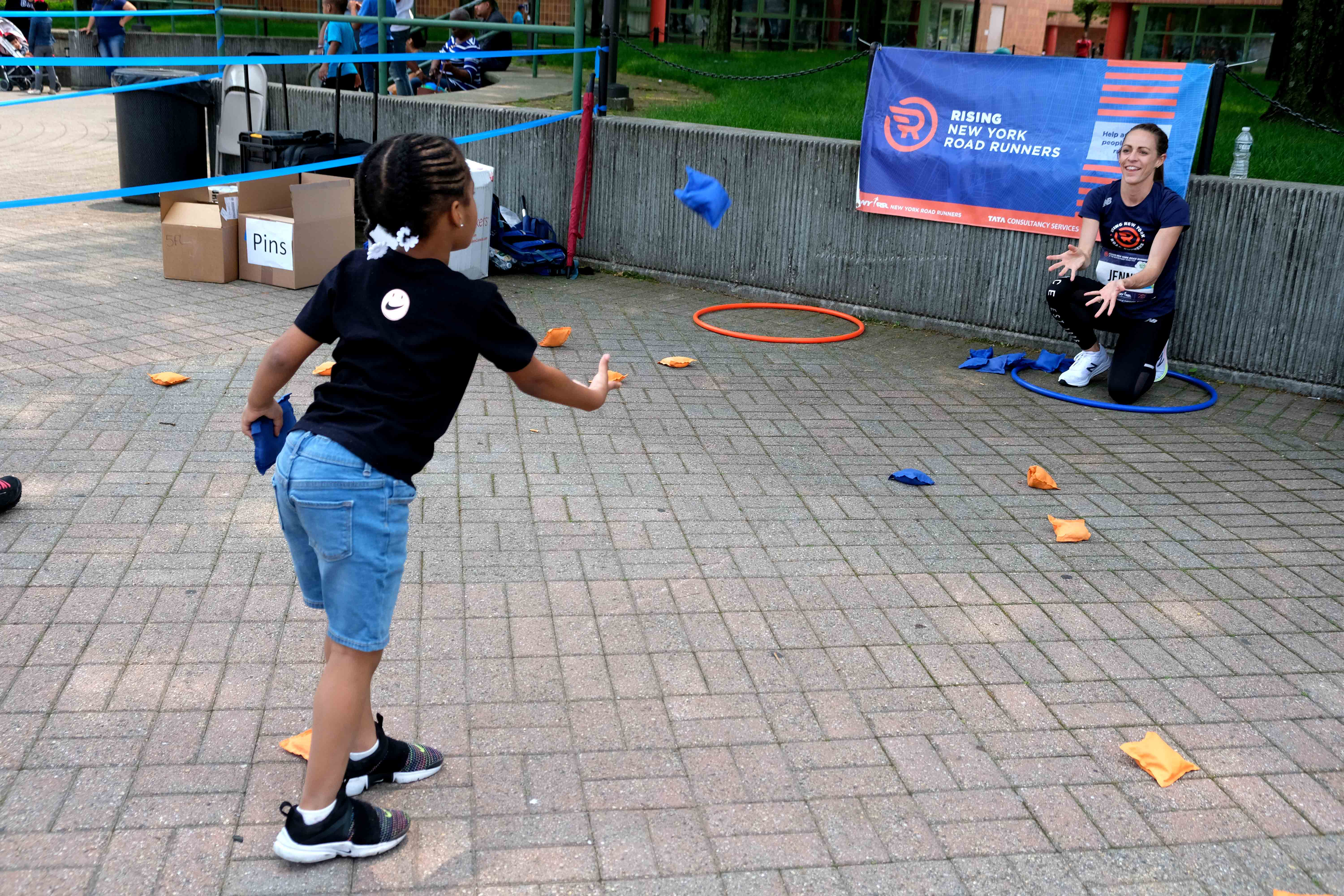 A Rising New York Road Runners student at a bean bag toss station with Jenny Simpson