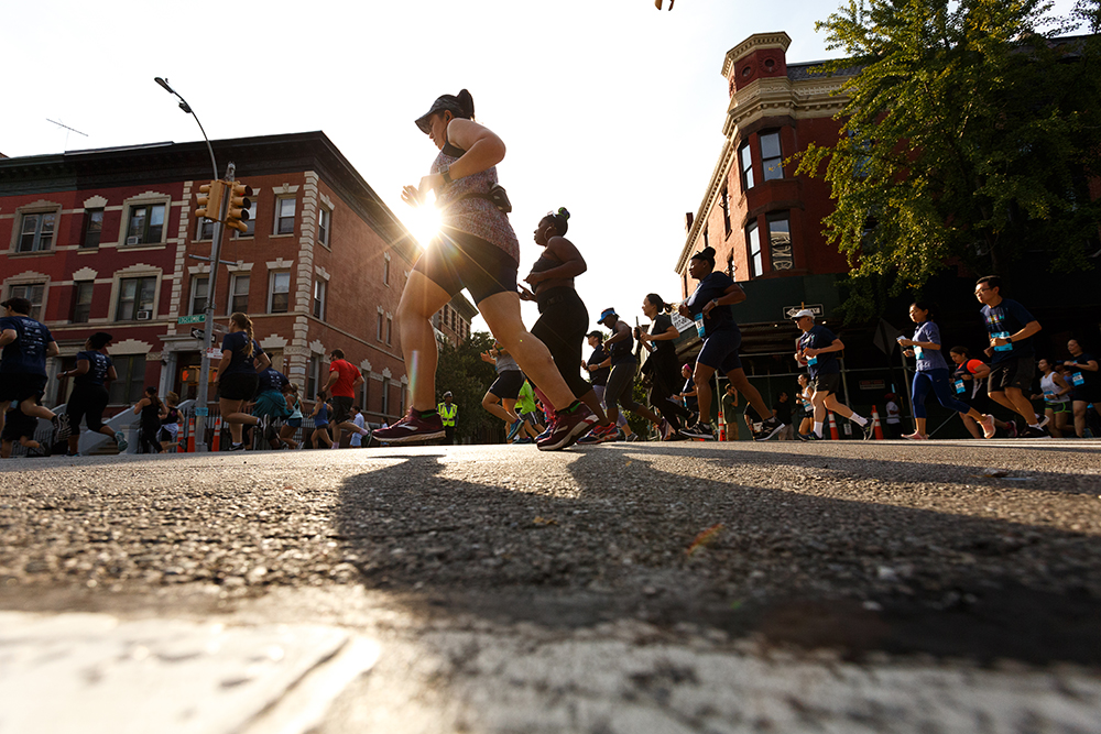 Runners running in front of a sunset on the streets of Harlem