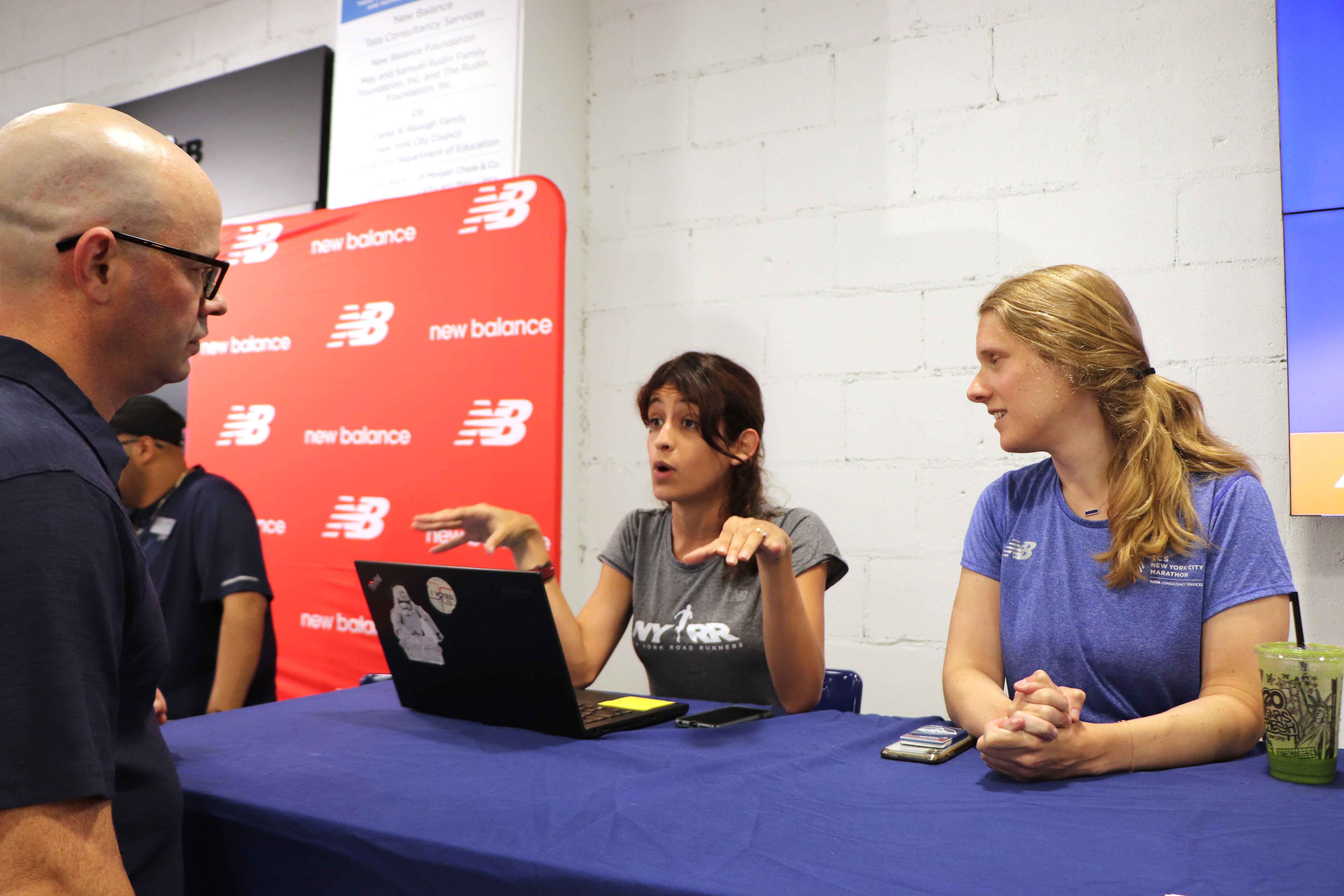 Two NYRR staff members speaking with a runner