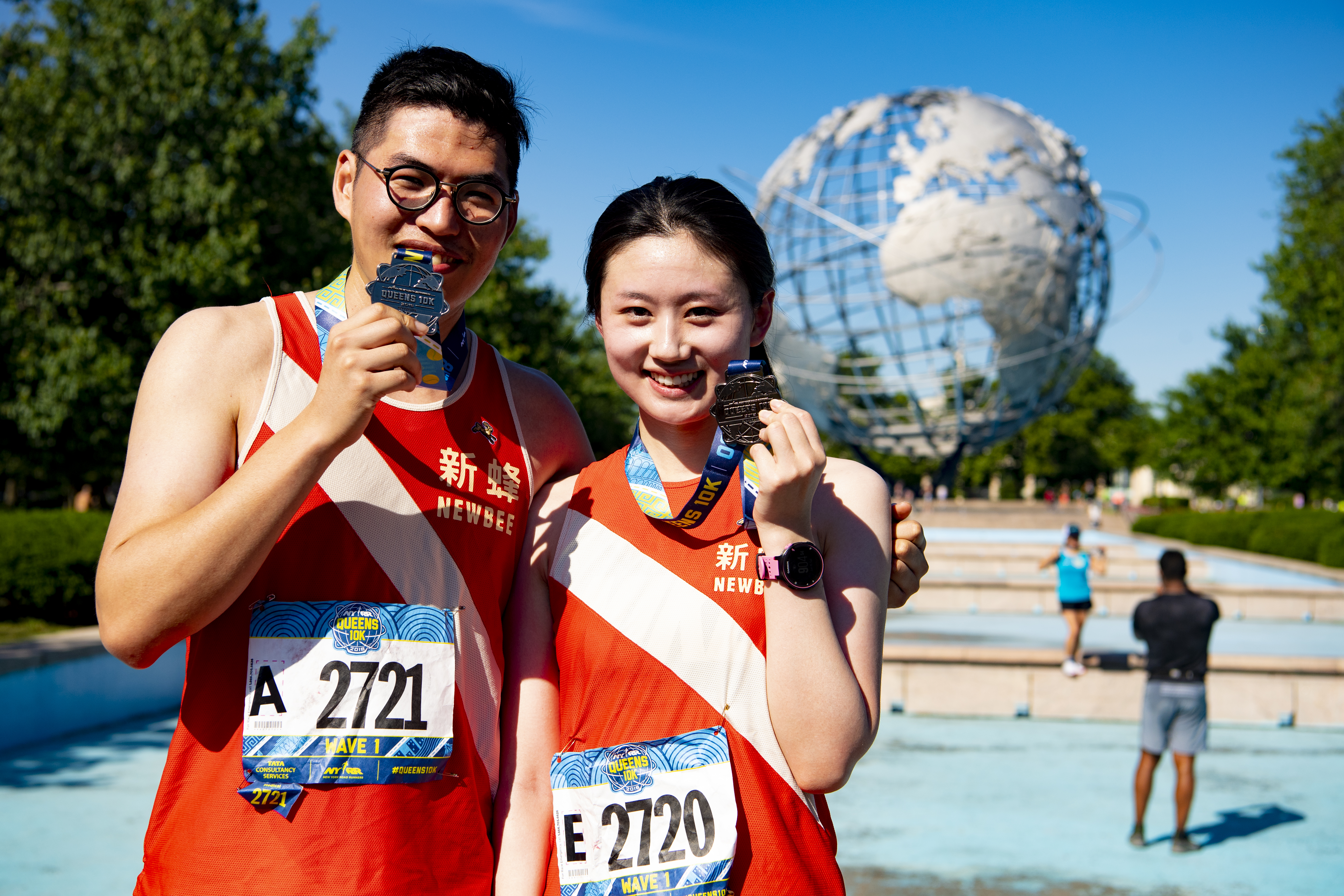Runners holding their NYRR Queens 10K finisher medals in front of the Unisphere in Flushing Meadows Corona Park