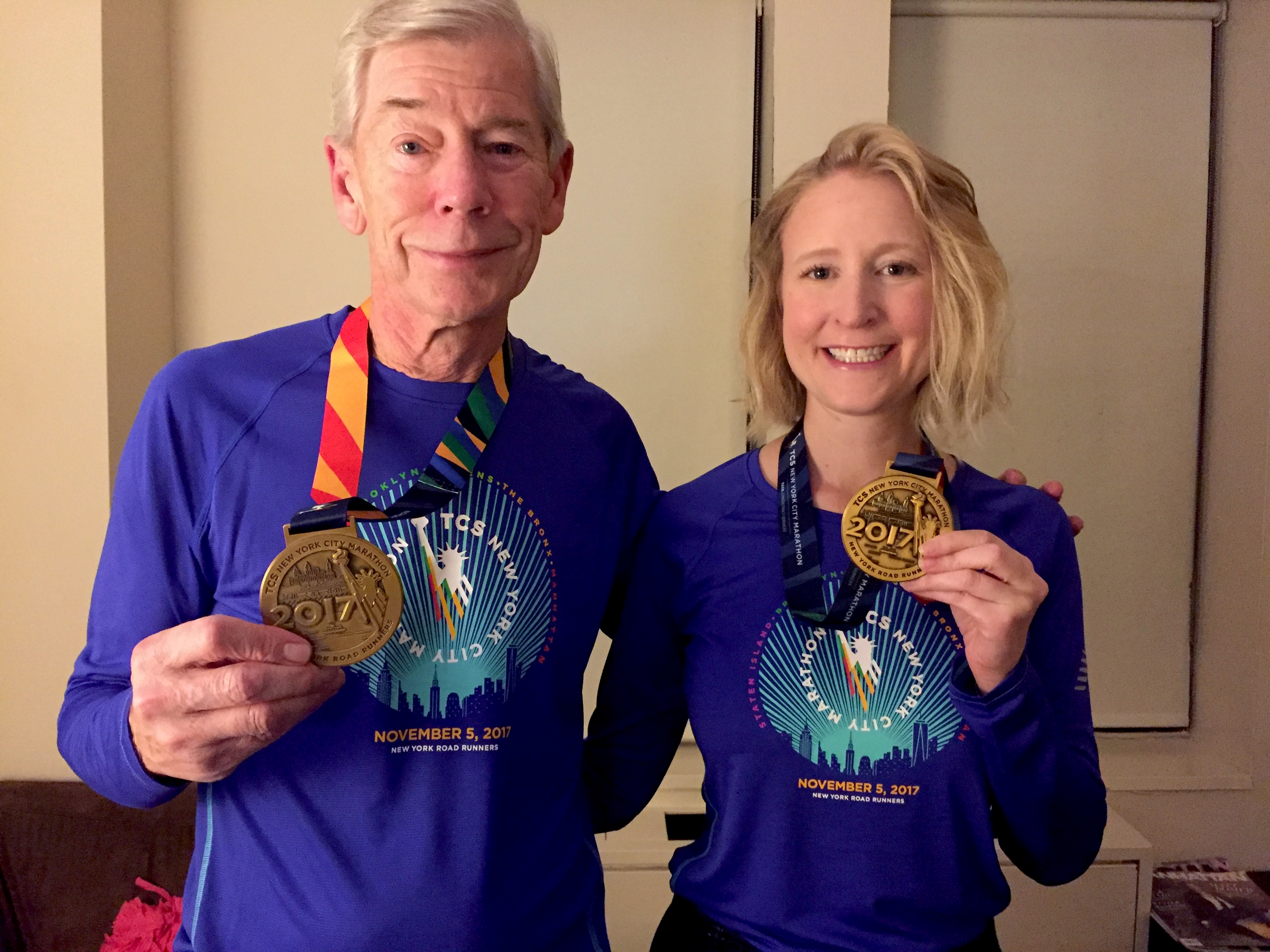 Two runners holding finisher medals from the TCS New York City Marathon