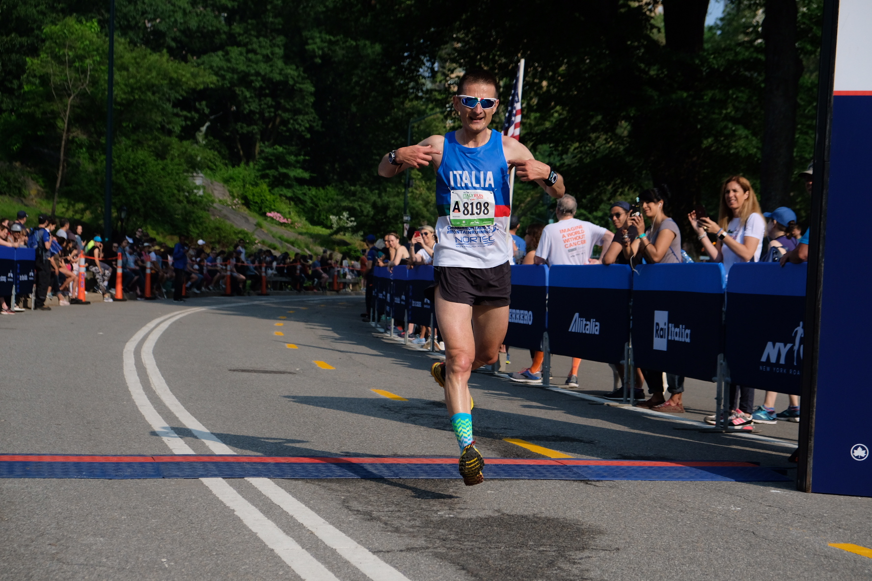 """A man finishing the Italy Run, wearing a singlet that says """"Italia"""""""