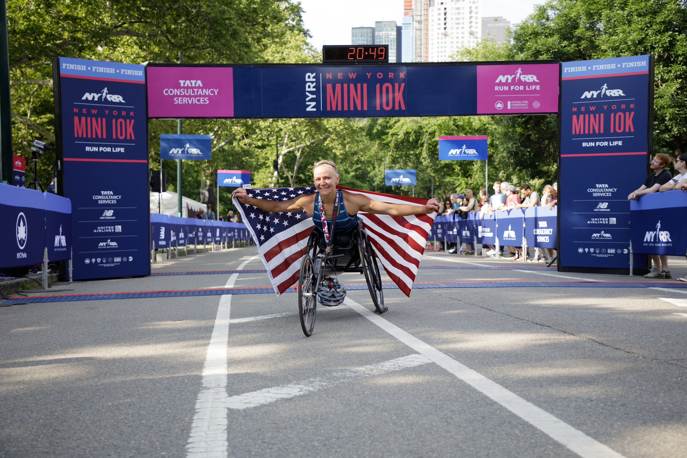 Susannah Scaroni after winning the 2018 New York Mini 10K holding the USA flag.