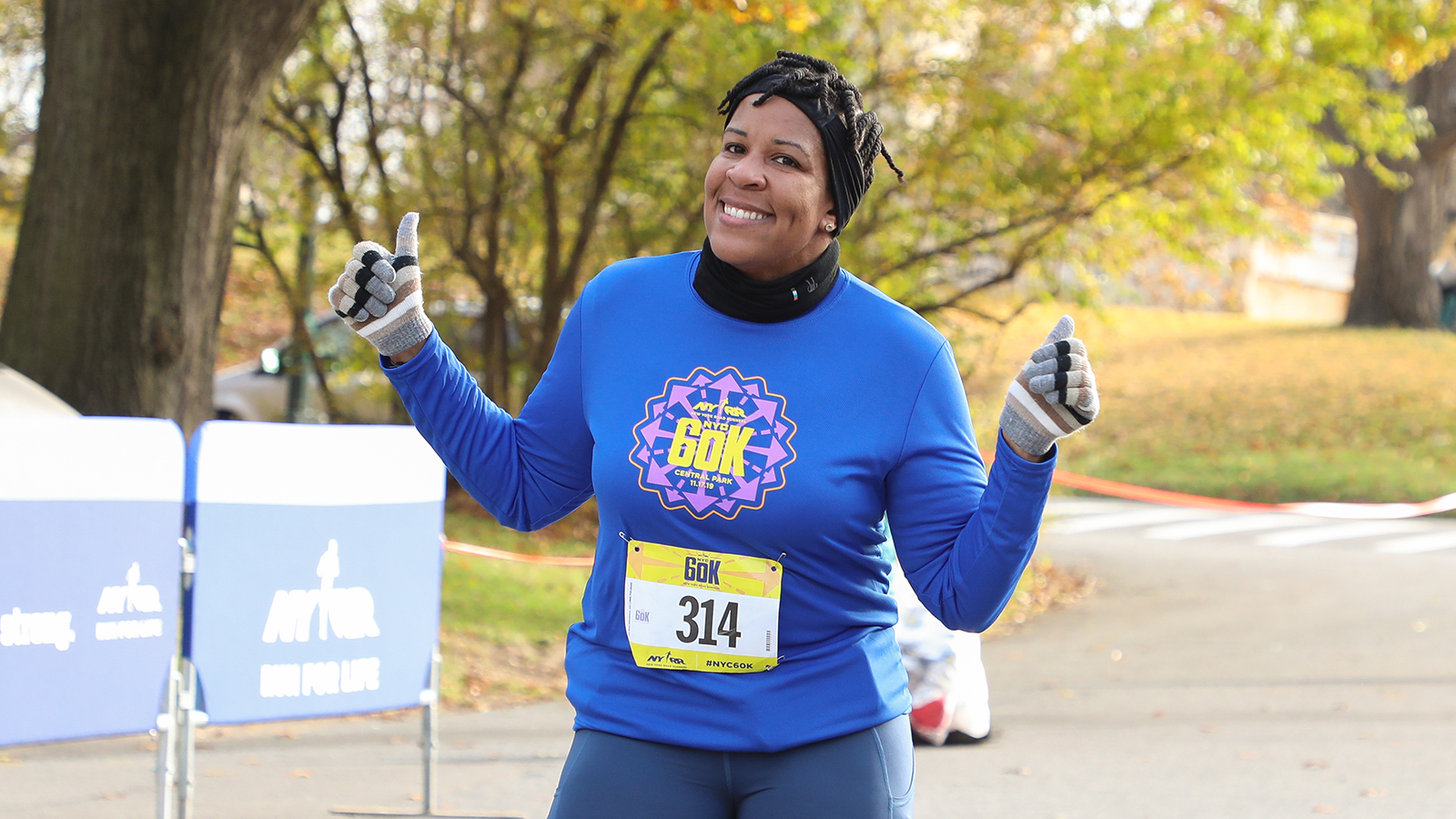 A woman running the NYRR 60K smiling during the race