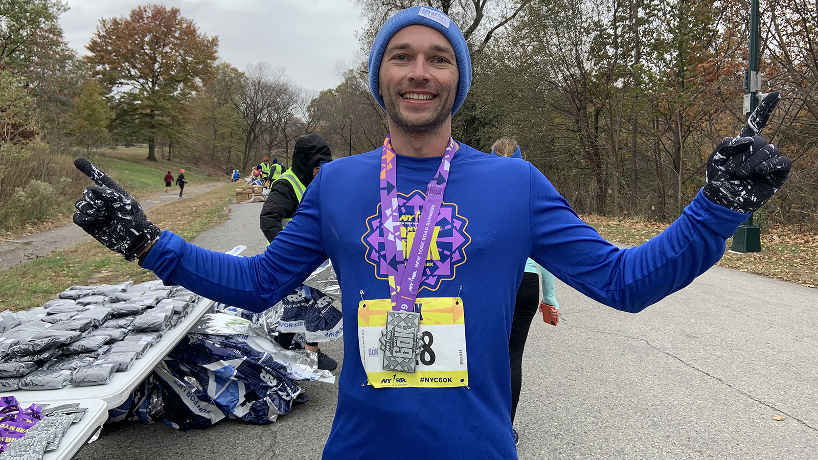 A runner posing with his medal after finishing the NYRR 60K