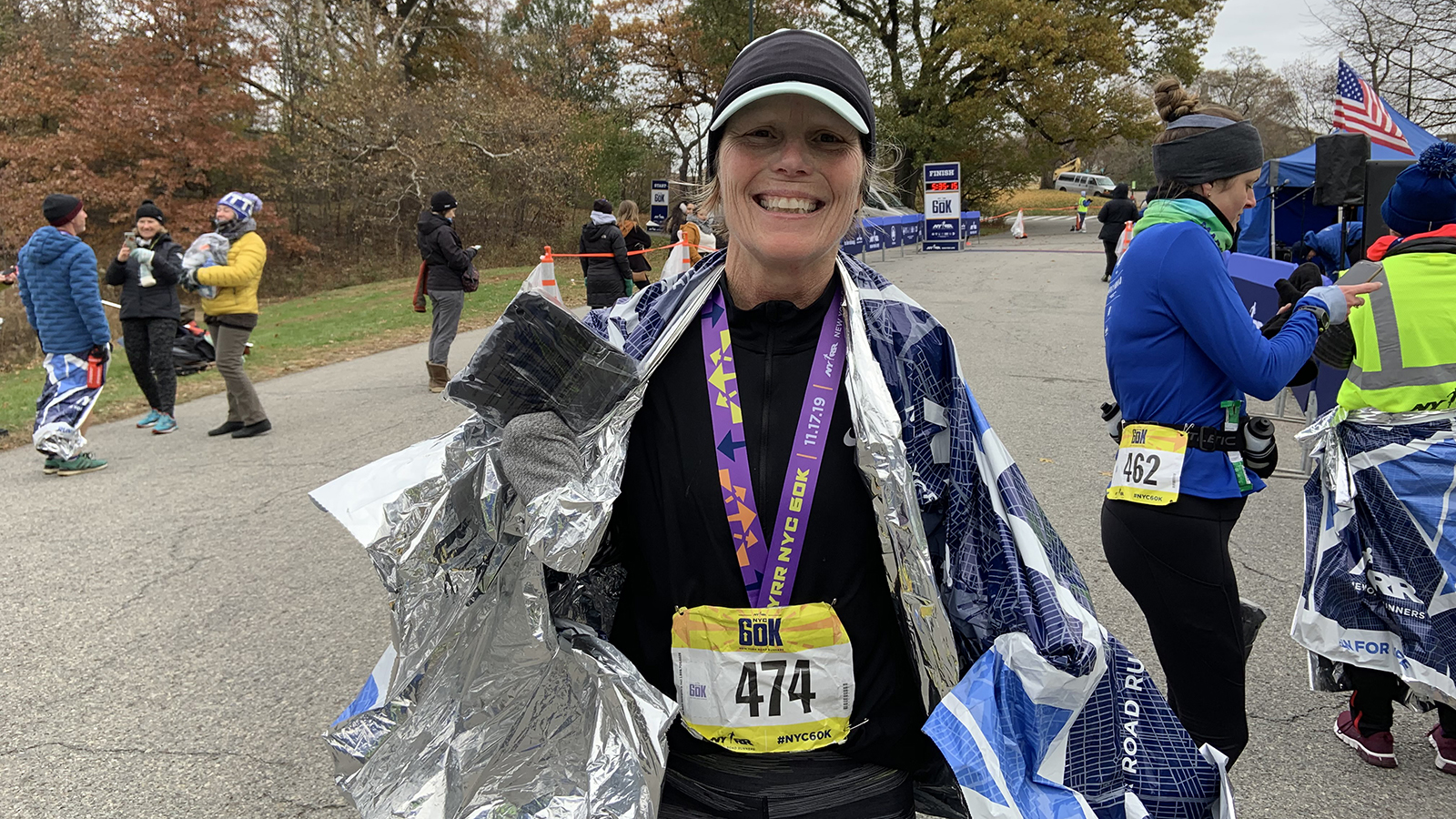 A woman after the NYRR 60K posing with her medal and souvenir backpack.
