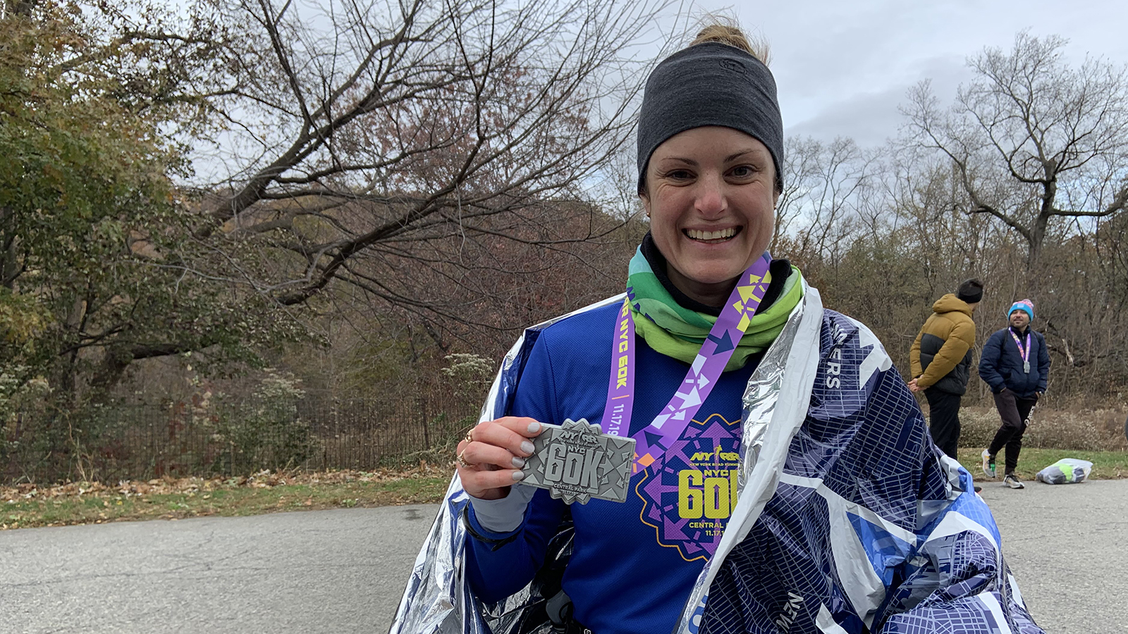 A runner posing with her medal after finishing the NYRR 60K