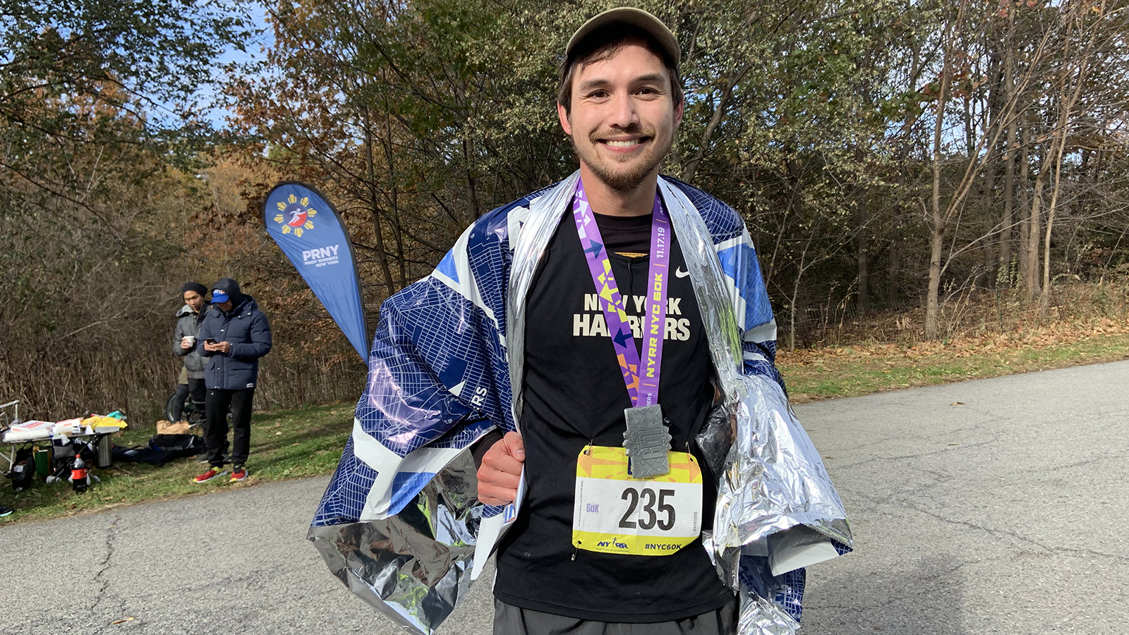 NYRR 60K runner smiling with his medal