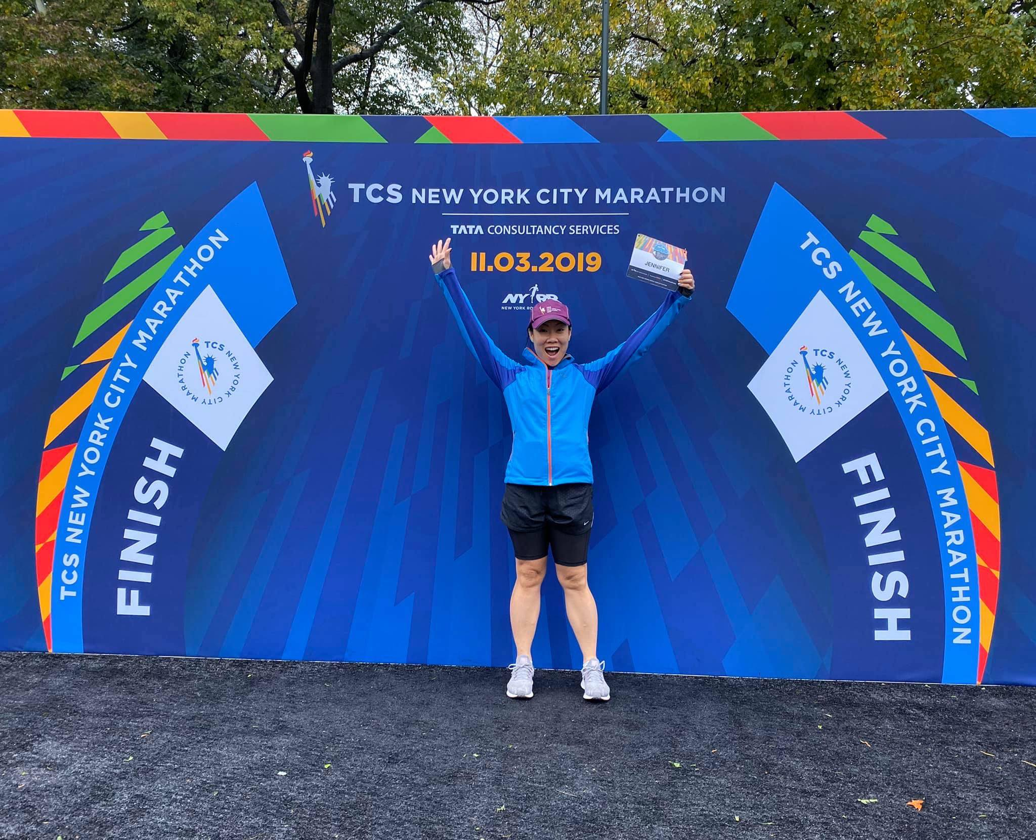 Jennifer Pyun holds her TCS NYC Marathon-Virtual 26.2M bib by the marathon finish line in Central Park.