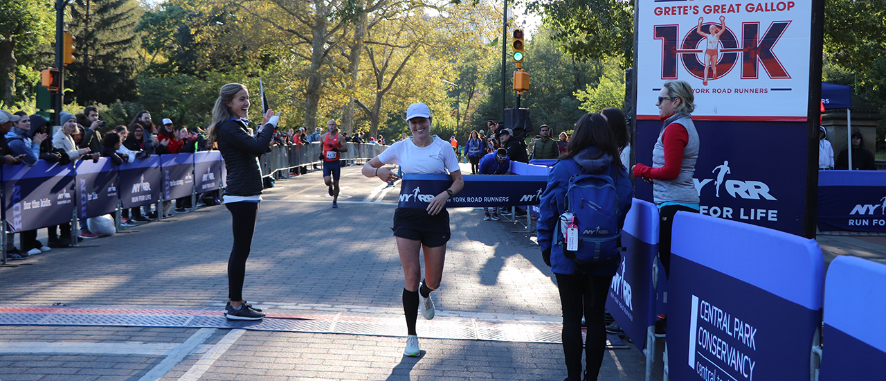Runner Rebeka Stowe breaking the tape at the 2019 NYRR Grete's Great Gallop
