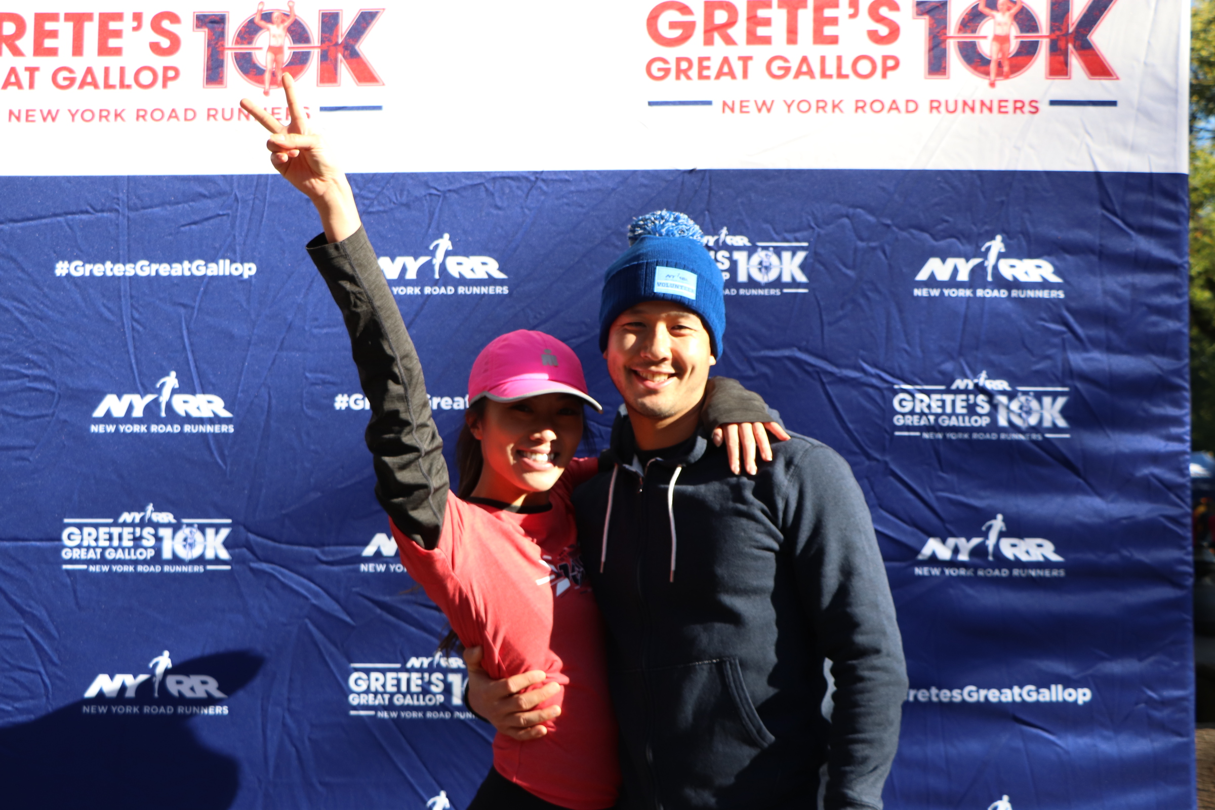 A man and a woman posing in front of the NYRR Grete's Great Gallop 10K Photo Booth