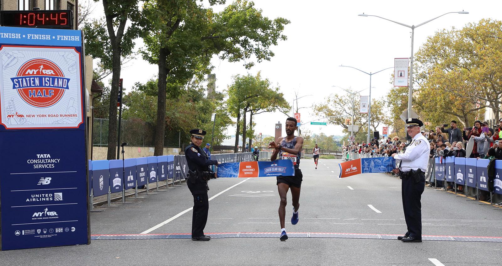 Tariku Demelash Abera breaks the tape at the Staten Island Half
