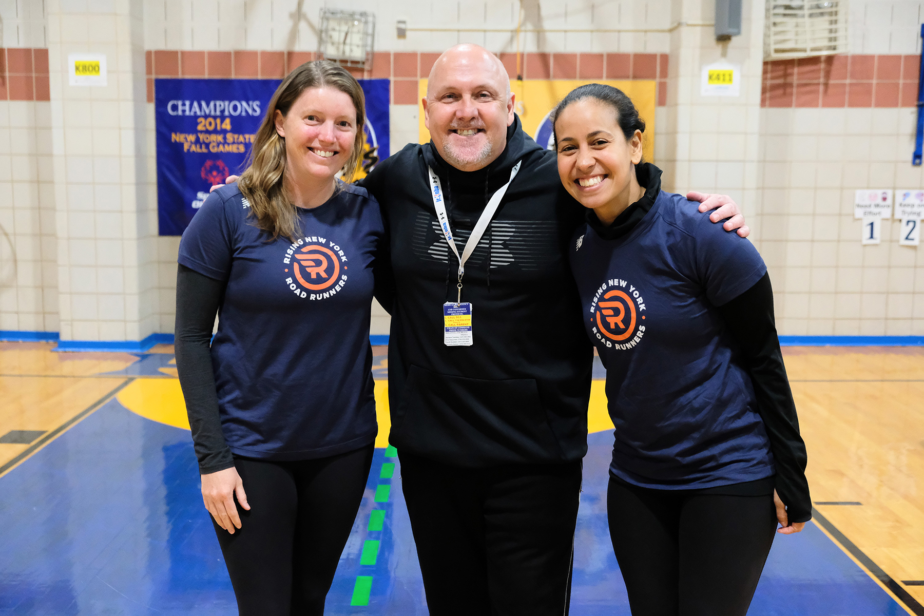 2019 Big Apple Award winner Doug Rebecca with NYRR's Caitlin Francisco and Lydia Gonzalez