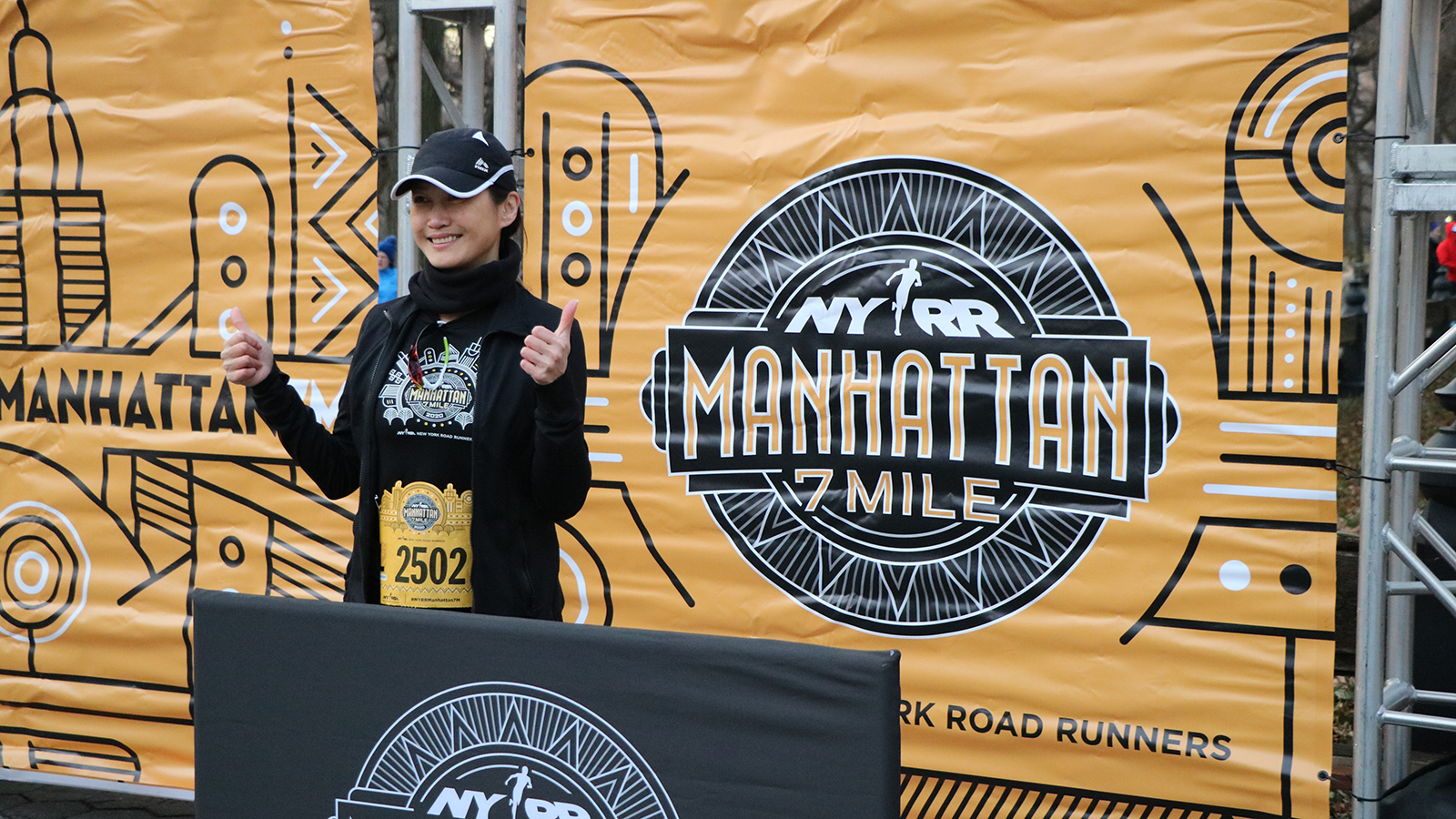 A runner posing in front of the NYRR Manhattan 7 Mile banner