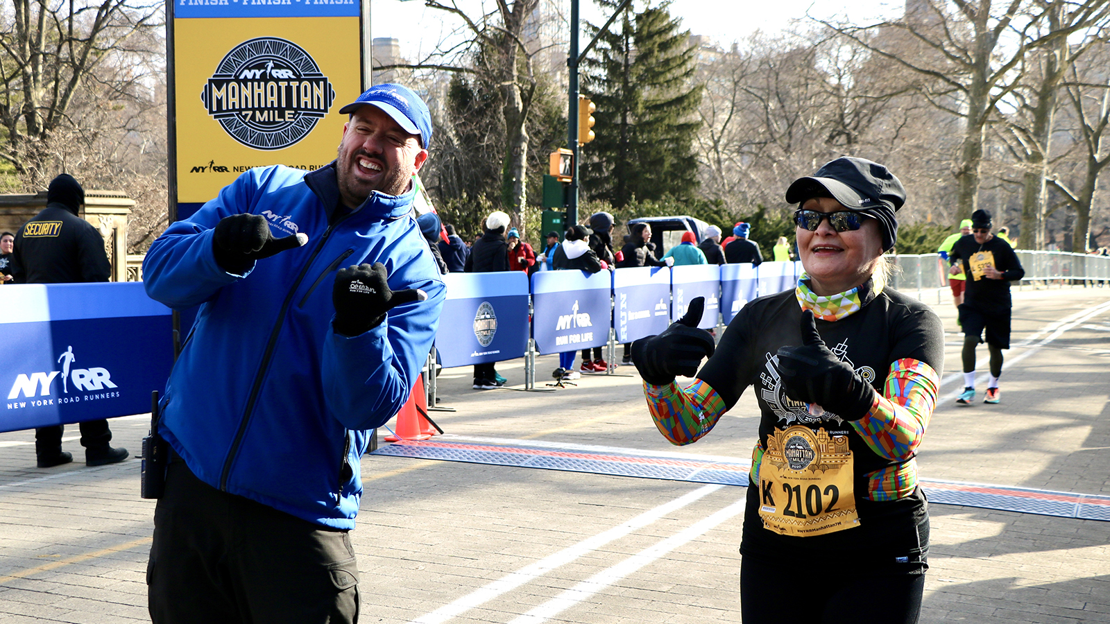 NYRR's Jim Heim with a runner at the finish line of the NYRR Manhattan 7 Mile