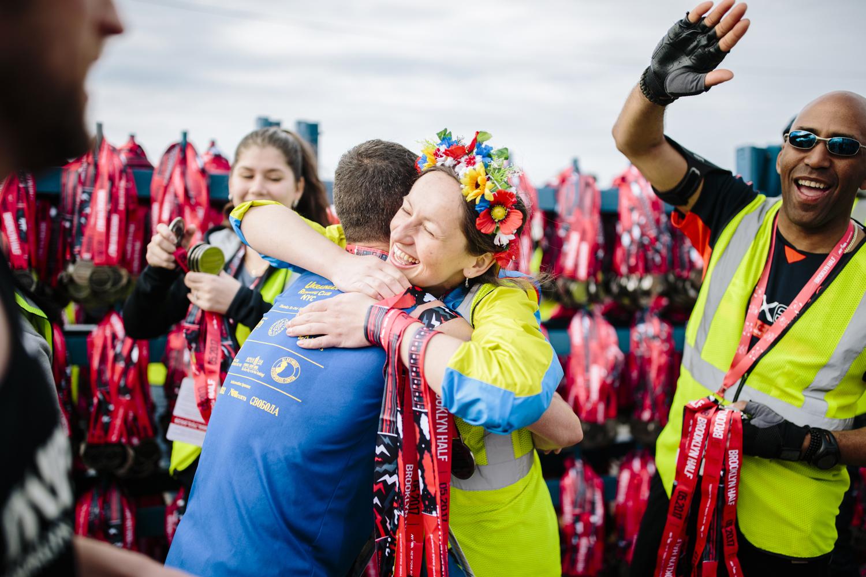 A volunteer hugging a runner after the Brooklyn Half