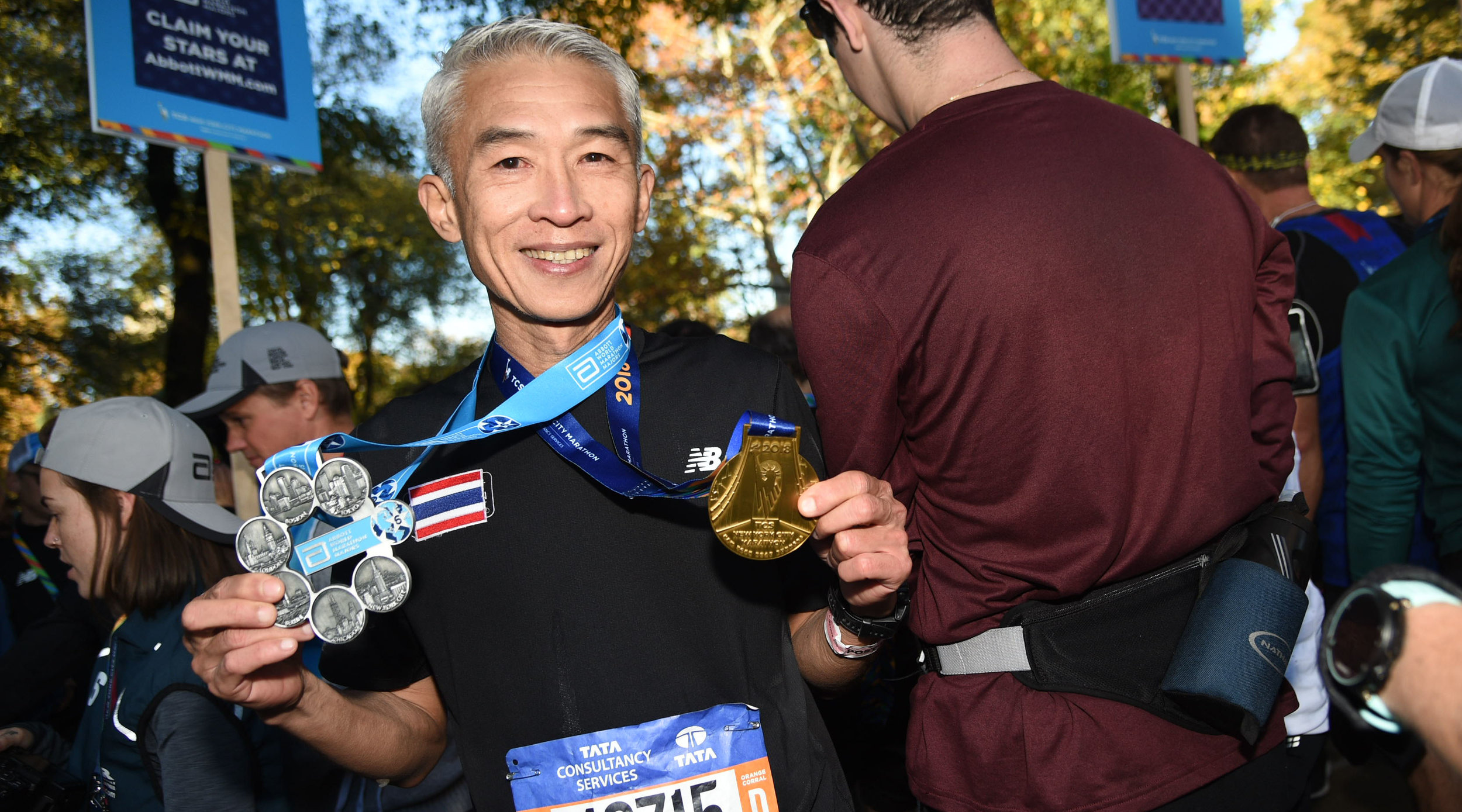 A runner holding his New York City Marathon finisher's medal along with his Abbott World Marathon Majors Six Star Finisher medal