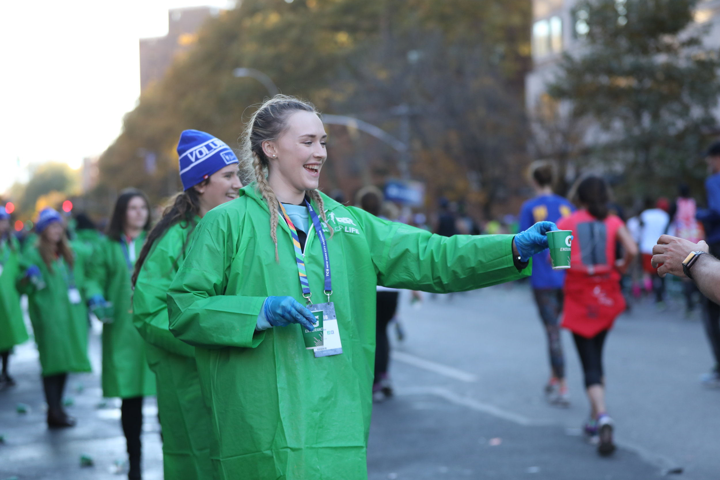 New York City Marathon volunteers handing out water at an aid station in Manhattan