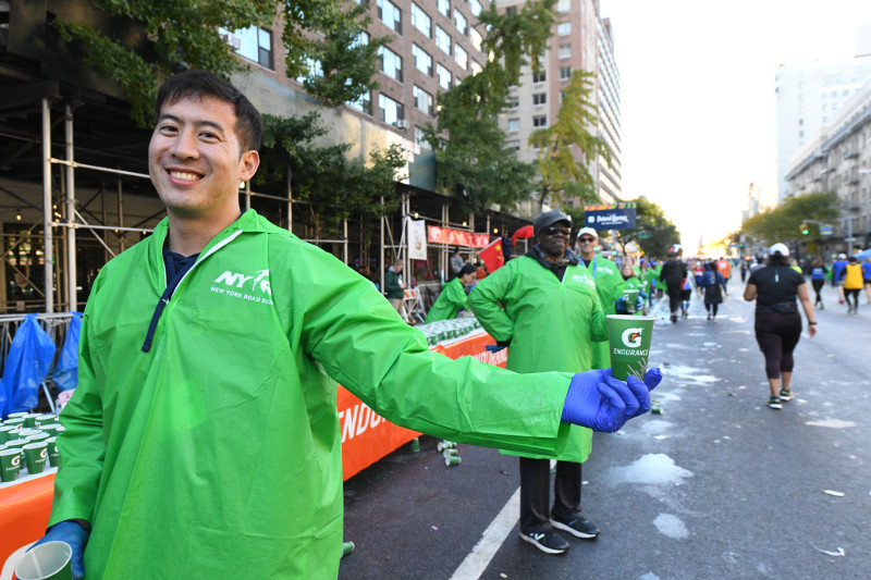 A New York City Marathon volunteer handing out water to runners at an aid station in Manhattan