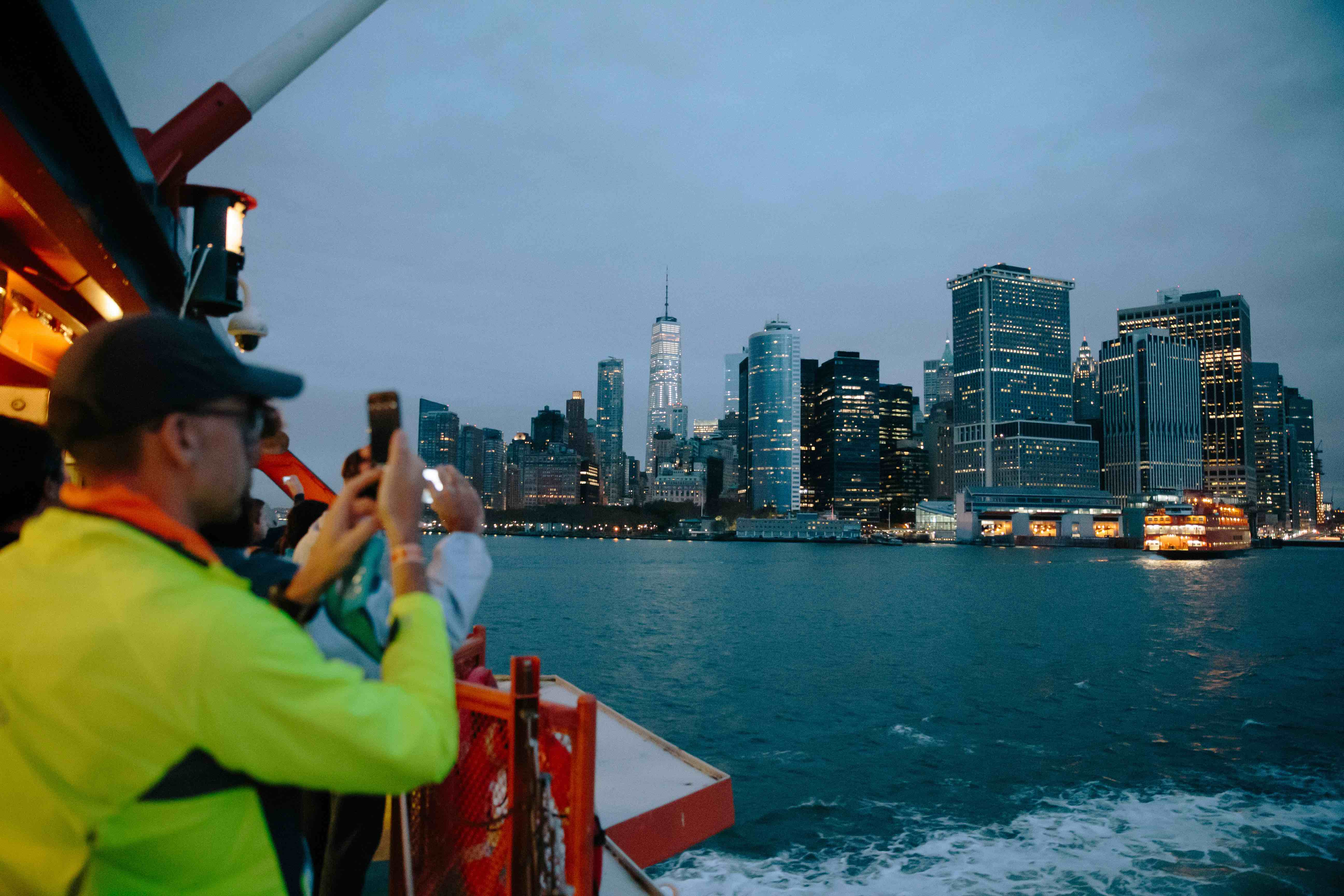 A TCS New York City Marathon runner taking a photo on the Staten Island Ferry, with the Lower Manhattan skyline in the background