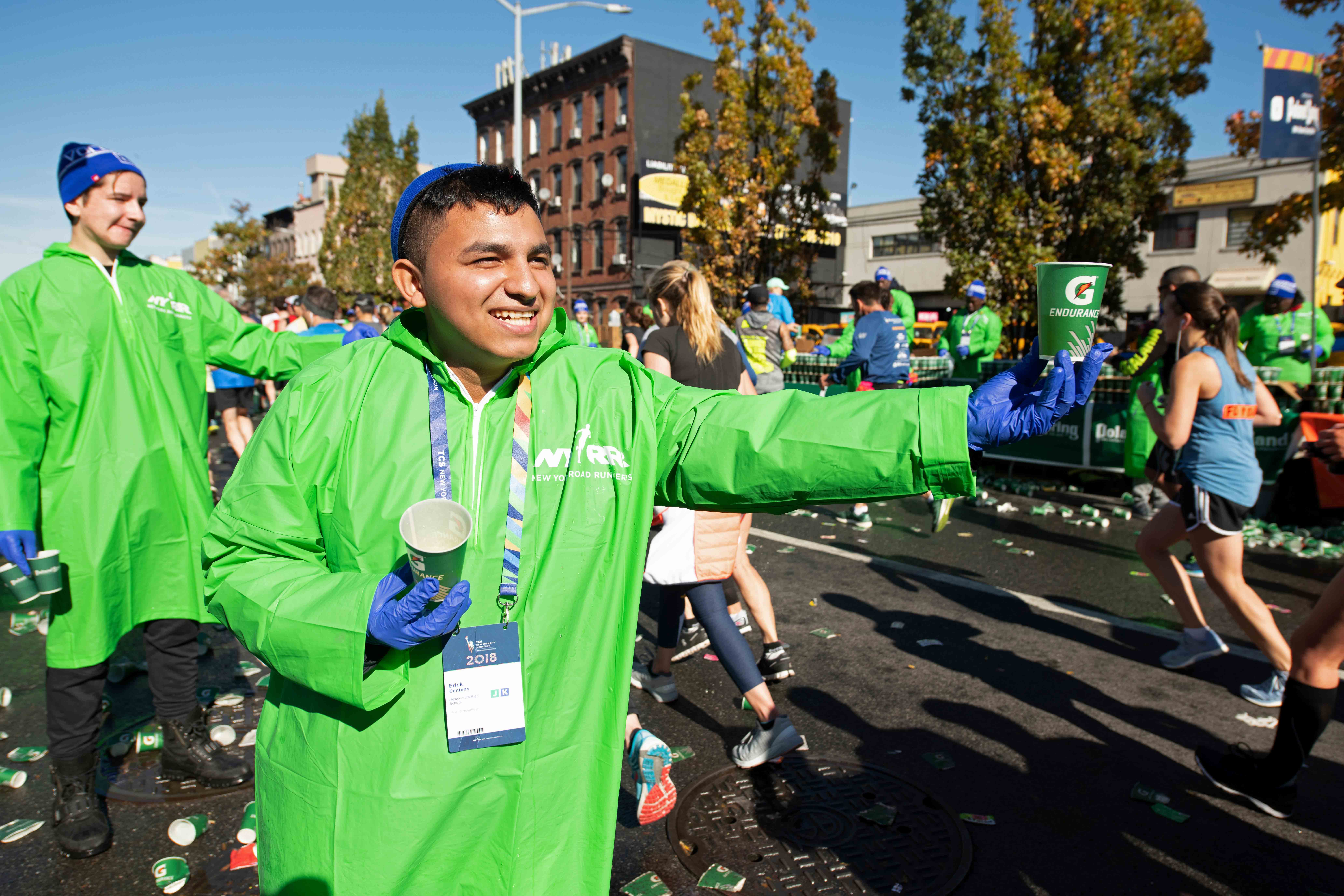 A TCS New York City Marathon volunteer holding out a Gatorade cup