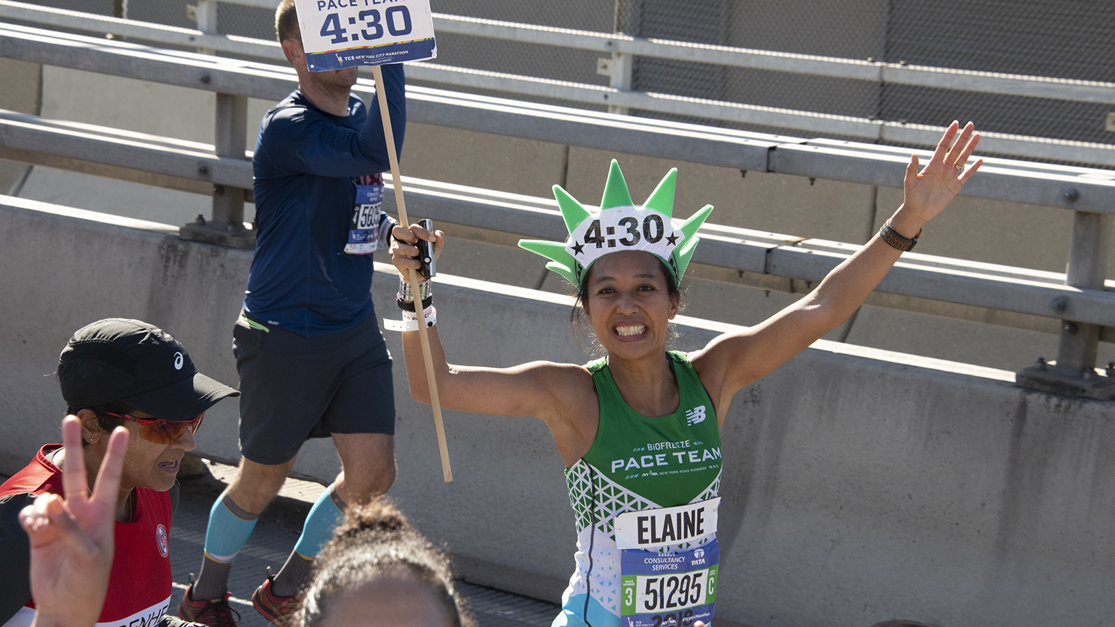 NYRR Pace Team member Elaine during the NYC Marathon with her pacing sign and wearing a statue of liberty hat