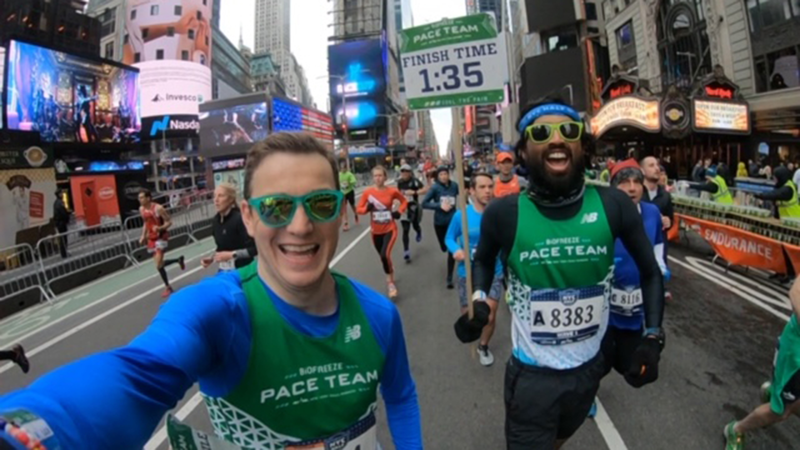 NYRR Pace Team members Stephen England and Devang Patel running through Times Square