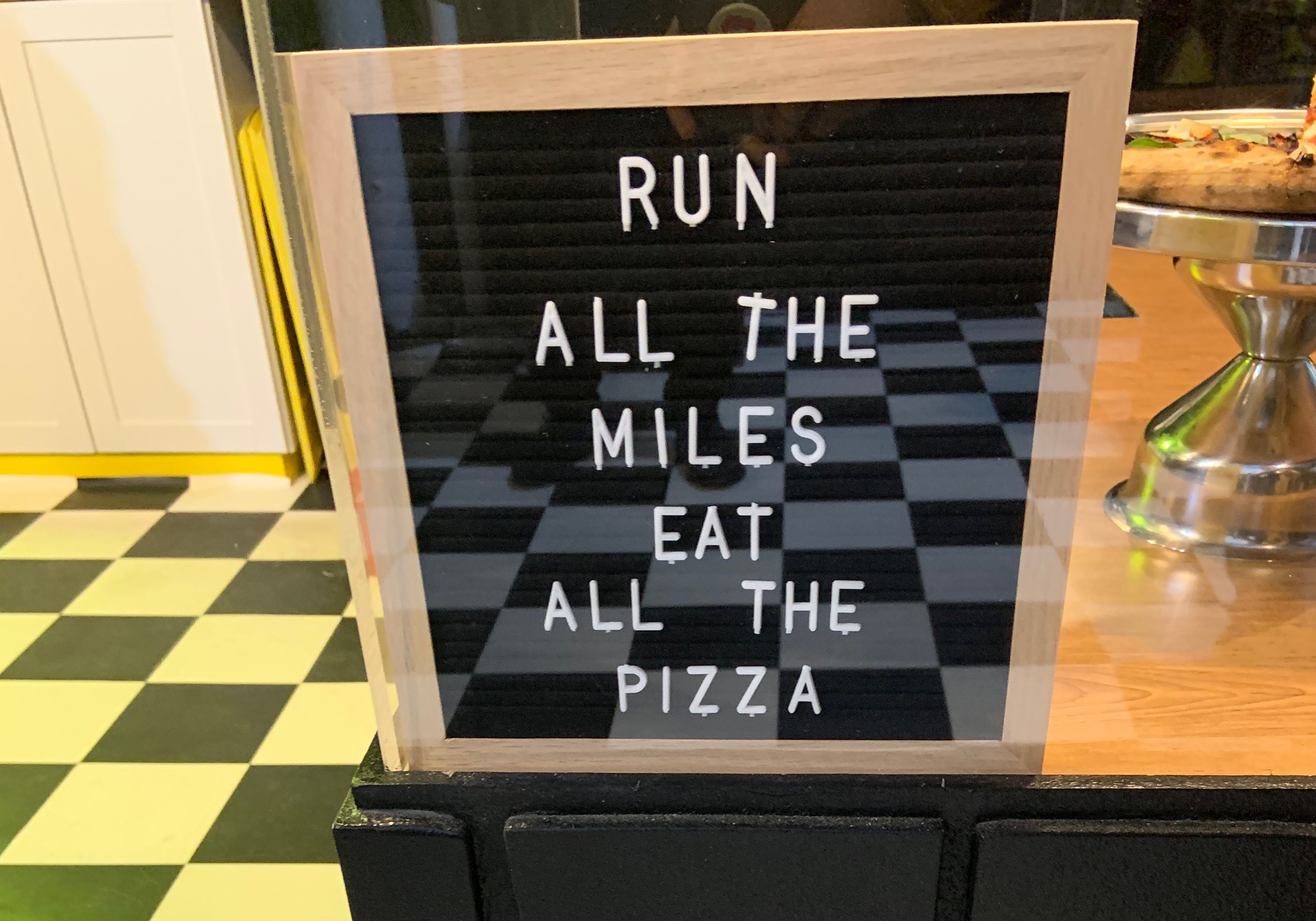 "A sign that says ""Run all the miles eat all the pizza"""