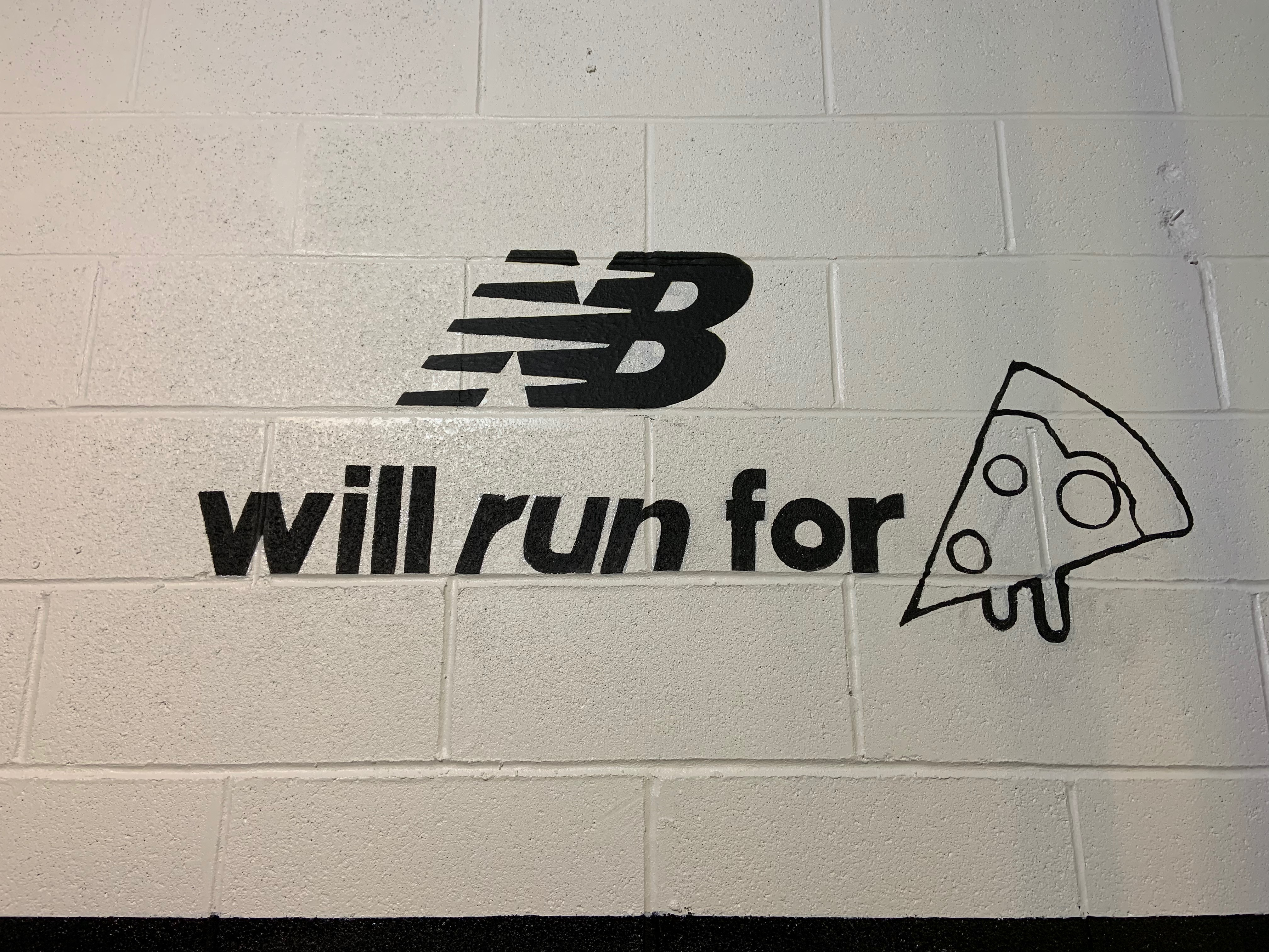 "New Balance logo and ""Will run for pizza"" spray painted on a white wall."