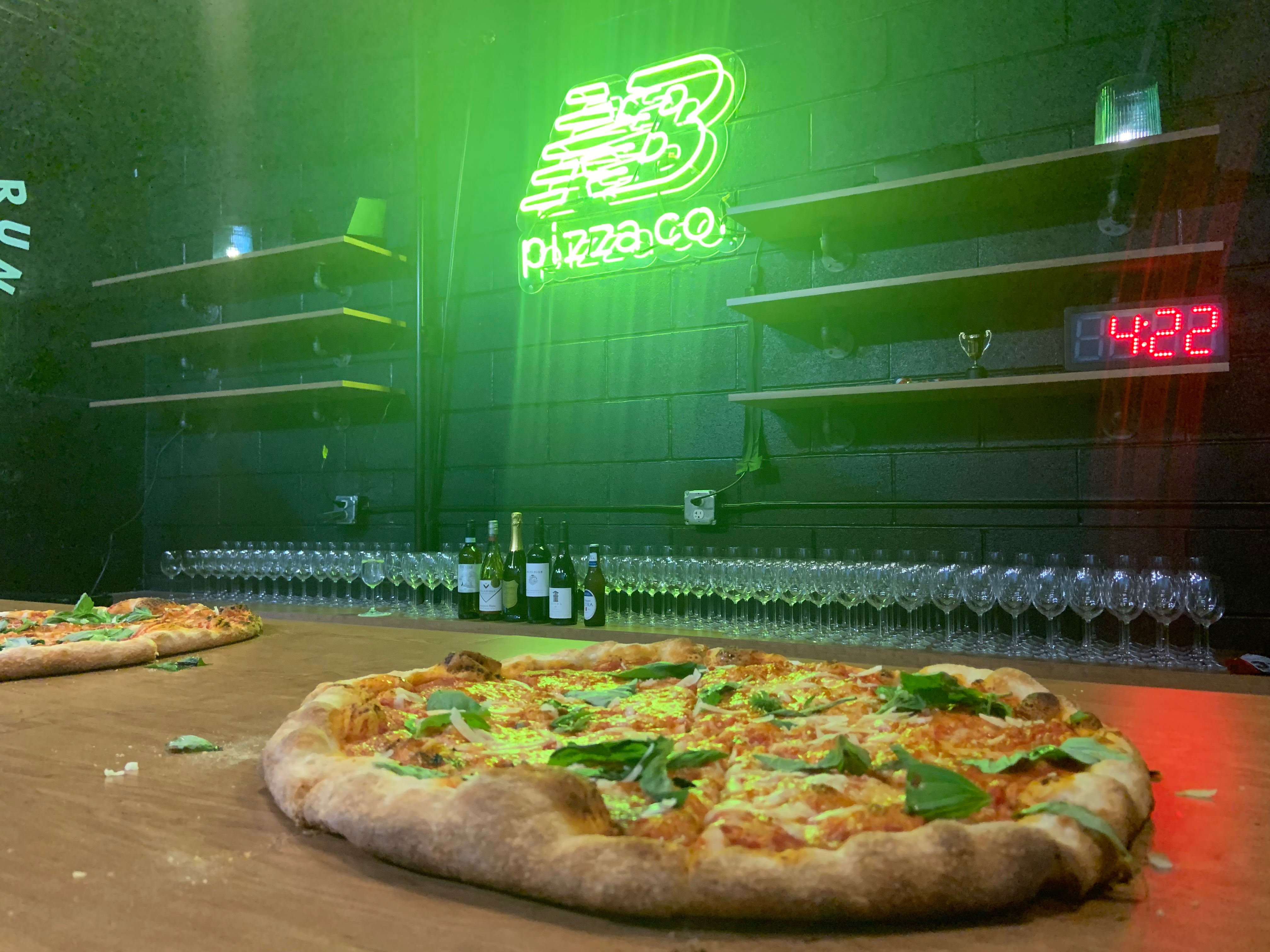 A pie of pizza on a bar in front of a neon green New Balance logo sign
