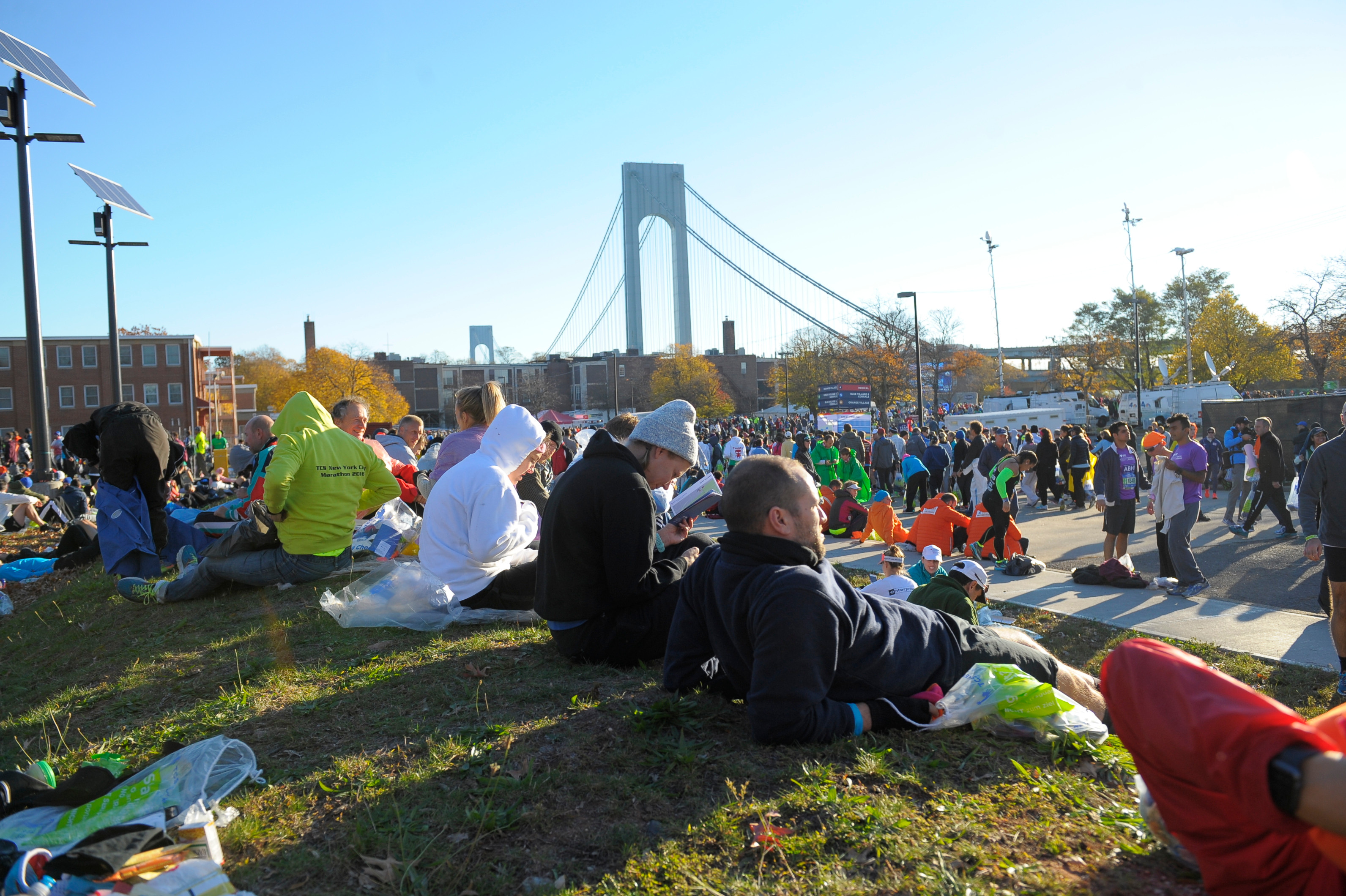 New York City Marathon runners sitting down and resting in the start area before their race begins