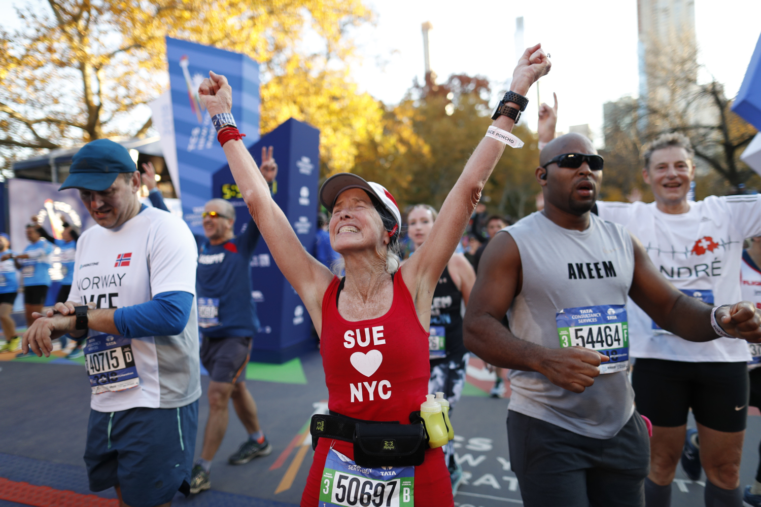 A runner celebrating after crossing the finish line of the New York City Marathon