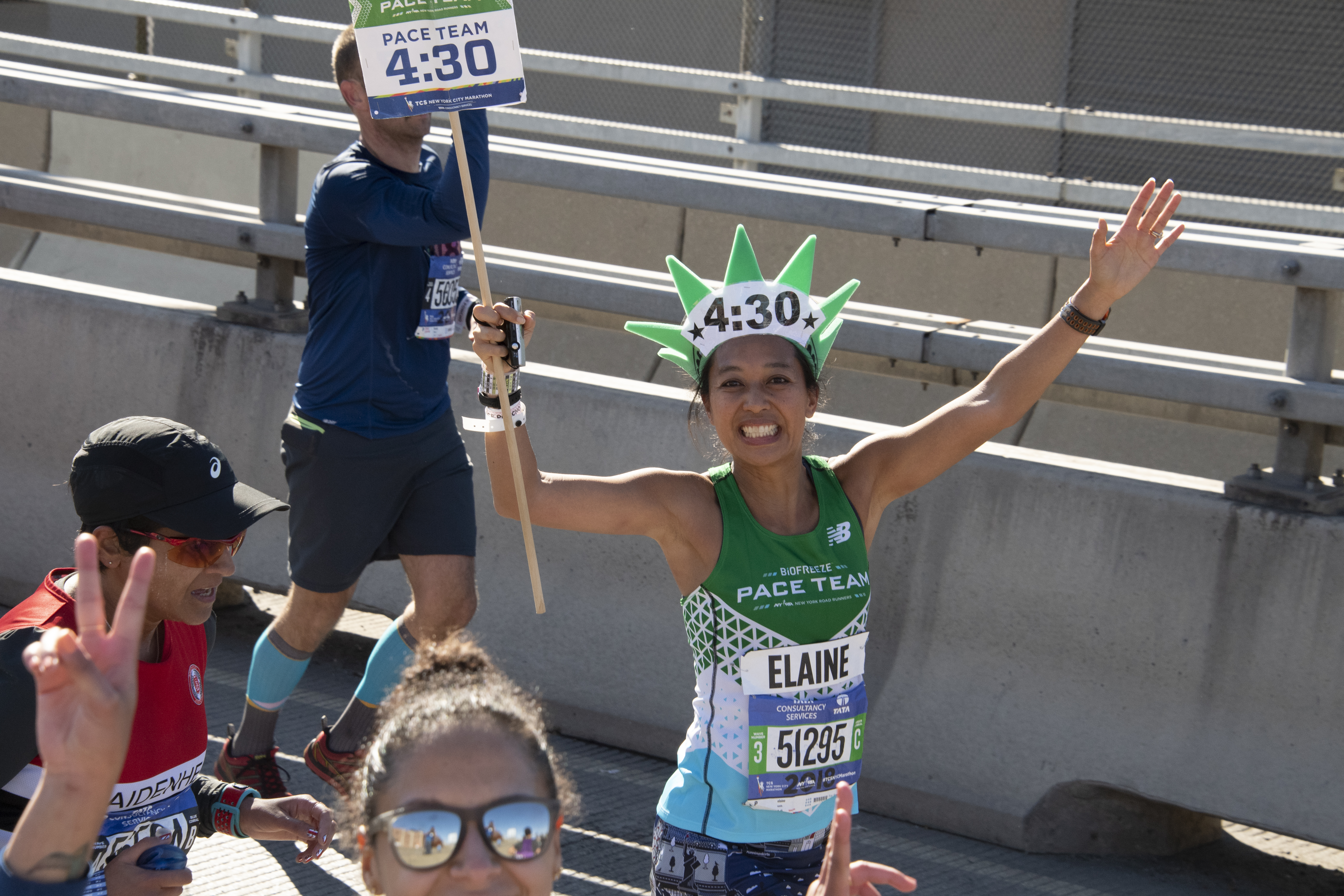 A member of the New York Road Runners pace team presented by Biofreeze guiding and holding up a sign for runners at the New York City Marathon