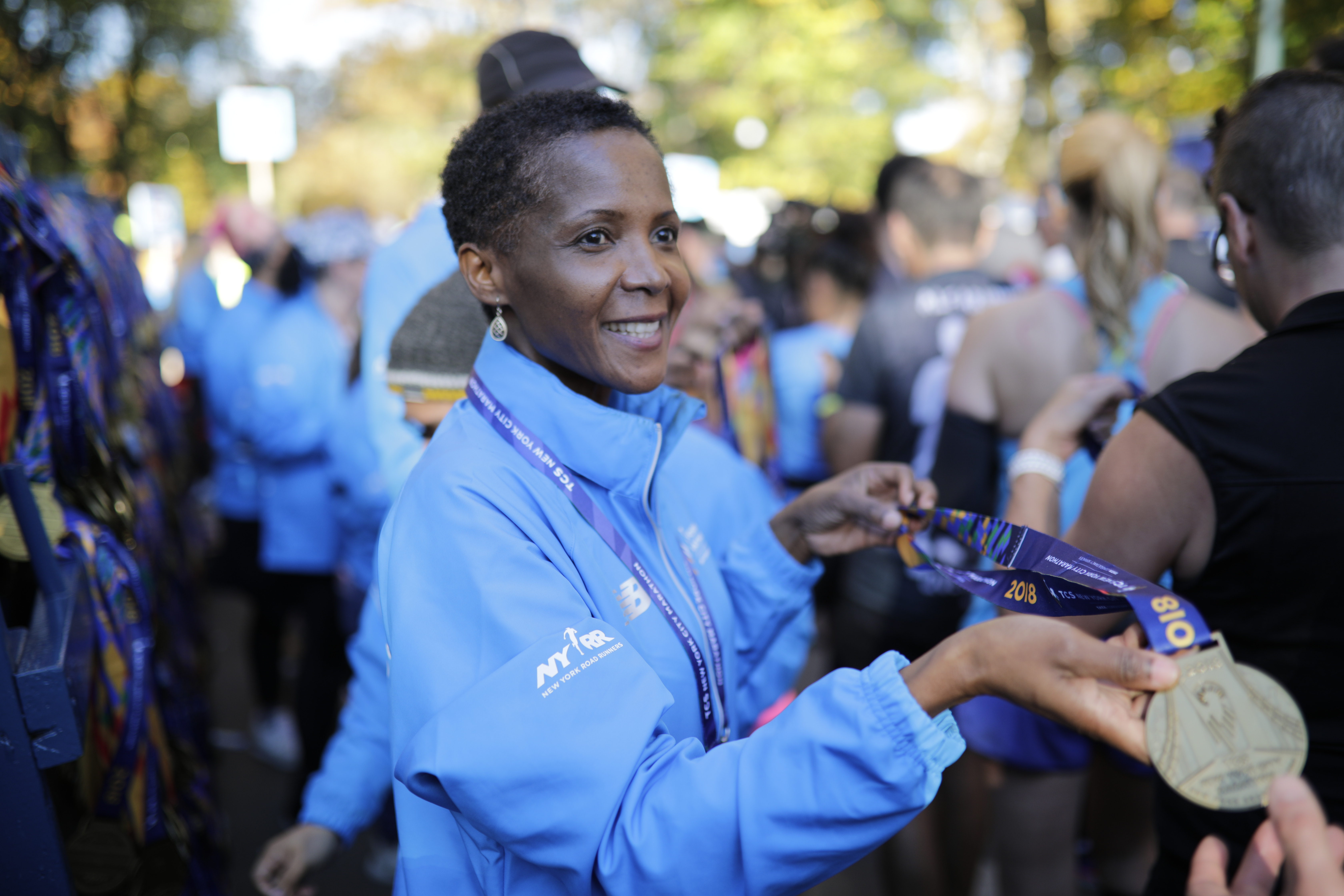 A volunteer handing out medals at the New York City Marathon finish area