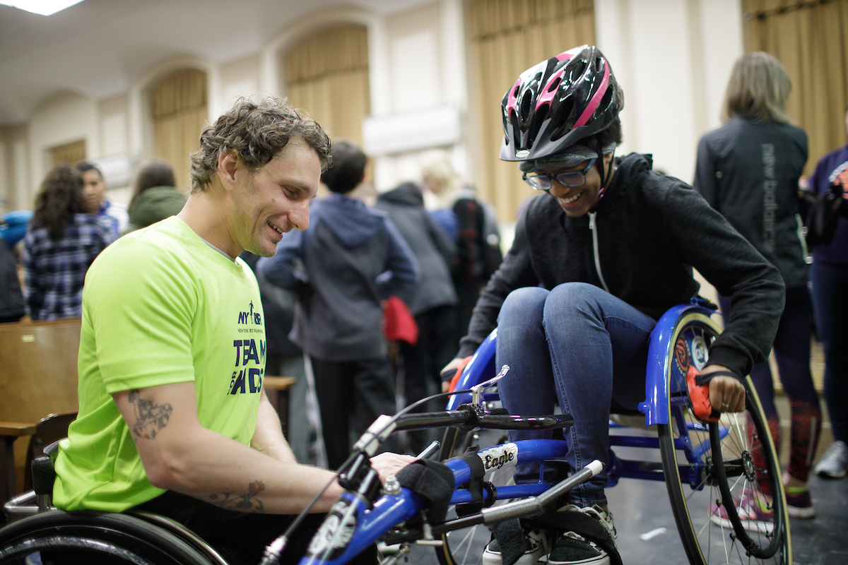 Josh George showing Rising New York Road Runners how to use a racing chair